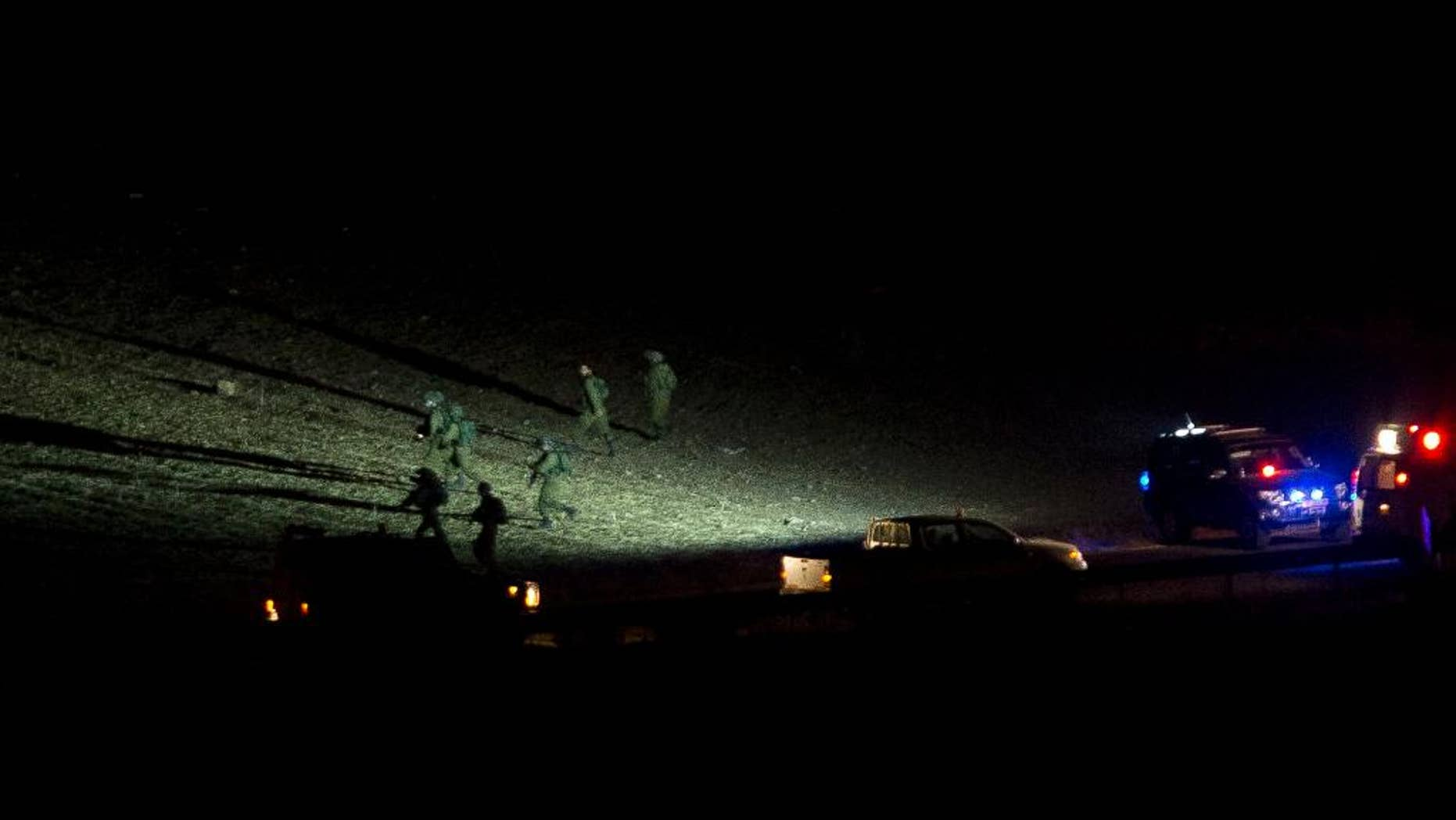 Israeli soldiers search the area of a shooting attack near Nablus, West Bank, Thursday, Oct. 1, 2015. Israeli military said that a Palestinian assailant shot and killed two parents driving with their four children along a West Bank road on Thursday. (AP Photo/Majdi Mohammed)