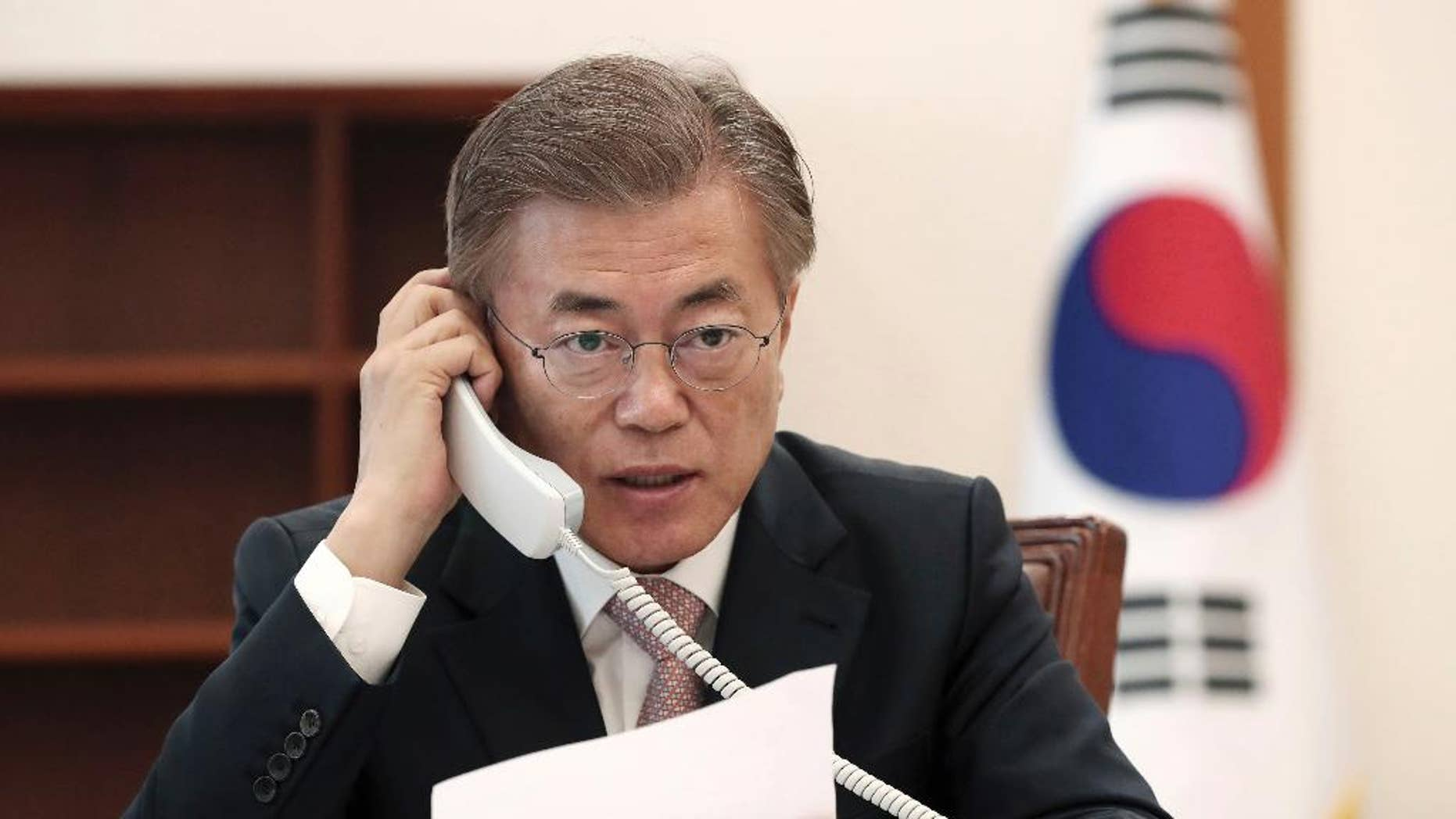 South Korean President Moon Jae-in talks on the phone with Chinese President Xi Jinping at the presidential Blue House in Seoul, South Korea, Thursday, May 11, 2017. Moon told his Chinese counterpart that he plans to send a special delegation to Beijing for talks on North Korea and a contentious U.S. missile-defense shield, Seoul officials said Thursday. (Yonhap via AP)