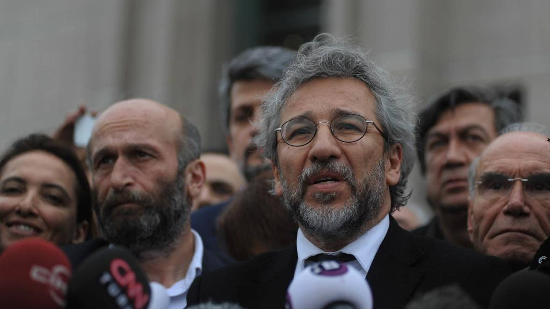 Can Dundar, the editor-in-chief of opposition newspaper Cumhuriyet, right, and Erdem Gul,  left, the paper's Ankara representative, speak to the media after their trial in Istanbul, Friday, March 25, 2016. The trial of two Turkish journalists accused of revealing state secrets and helping a terrorism organization over their reports on alleged government-arms smuggling to Syrian rebels was adjourned on Friday after opposition lawmakers refused to leave the courthouse in defiance of a controversial ruling to proceed behind closed doors.(AP Photo/Omer Kuscu)
