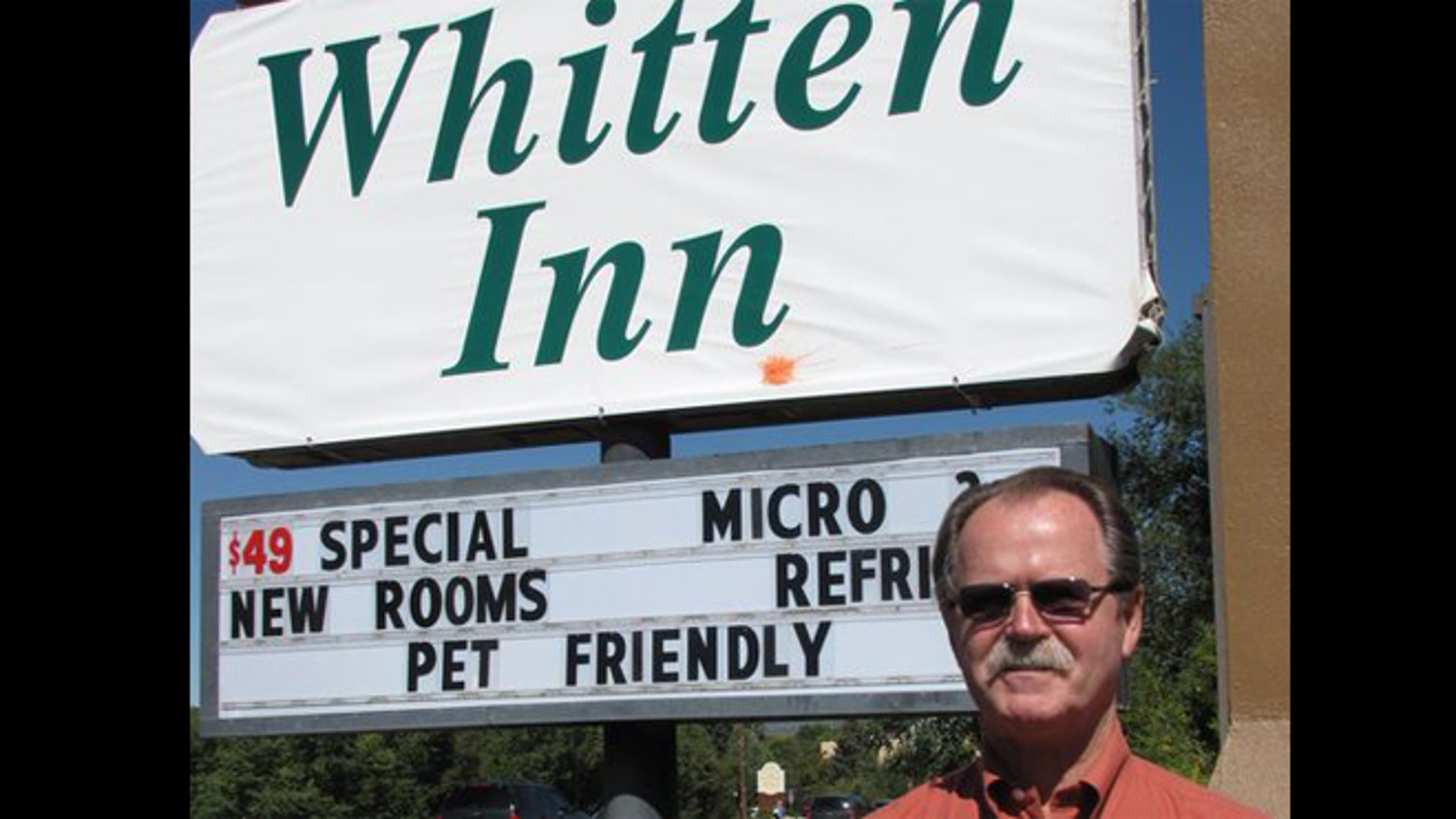 This Oct. 1, 2009 photo shows hotel owner Larry Whitten standing in front of the sign for his hotel in Taos, N.M.