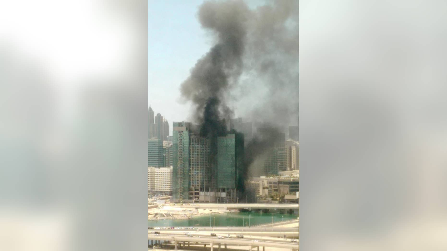 In this photo provided by Hasan Qureshi, smoke rises from a blaze that broke out in a high-rise building under construction in Abu Dhabi, United Arab Emirates, Tuesday, Aug 30, 2016. Cities in the fast-developing Emirates have been hit by a spate of fires in recent years, including one in a residential tower in Dubai last month and another at a luxury hotel next to the city's biggest shopping mall on New Year's Eve. (Hasan Qureshi via AP)