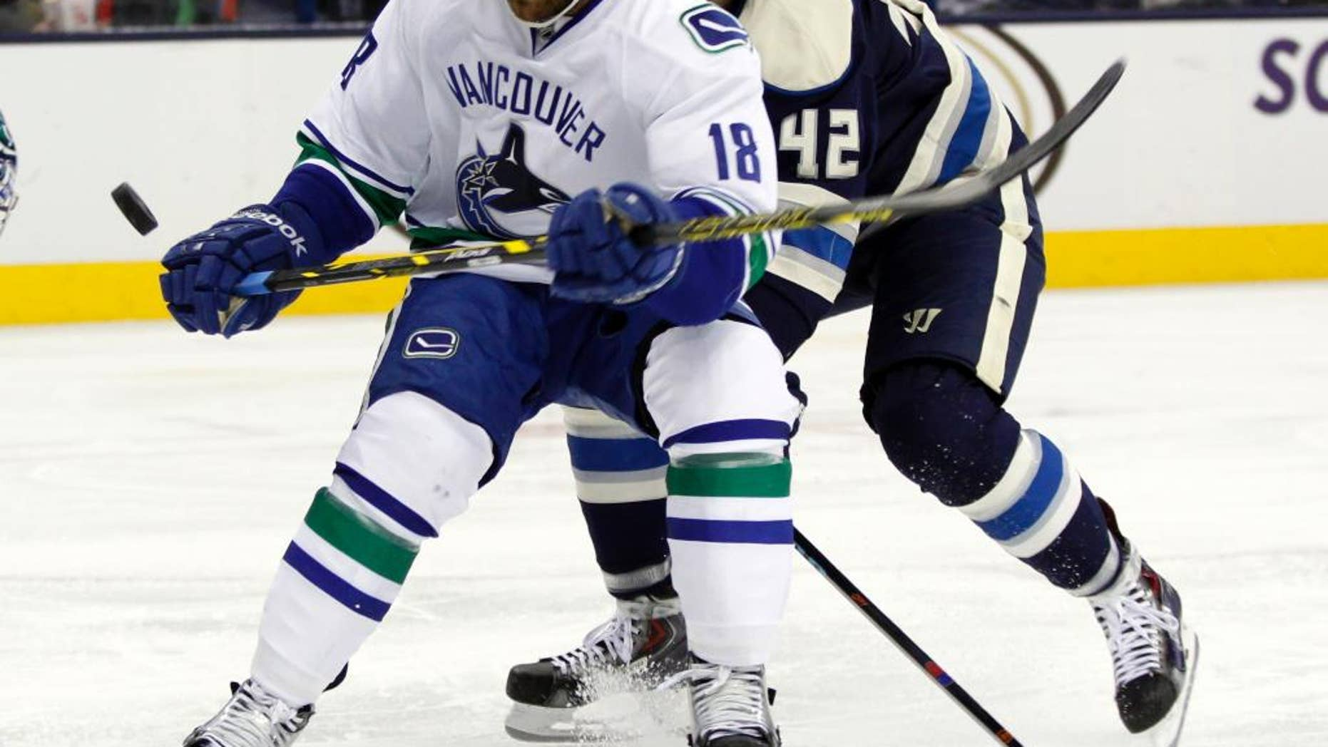 Vancouver Canucks' Ryan Stanton, left, works for the puck in front of Columbus Blue Jackets' Artem Anisimov, of Russia, during the second period of an NHL hockey game in Columbus, Ohio, Friday, Nov. 28, 2014. (AP Photo/Paul Vernon)