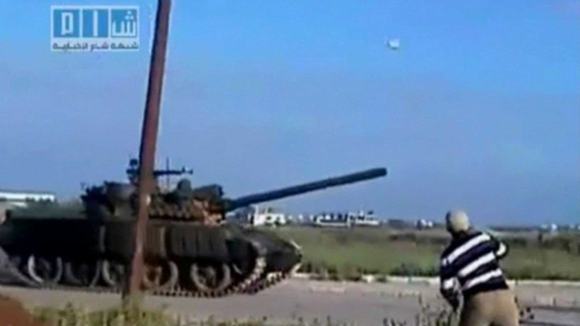 April 24: This video image taken from amateur video released by Sham News Network, a Syrian Freedom group, shows a man throwing an object at a tank in Daraa, Syria. (AP)
