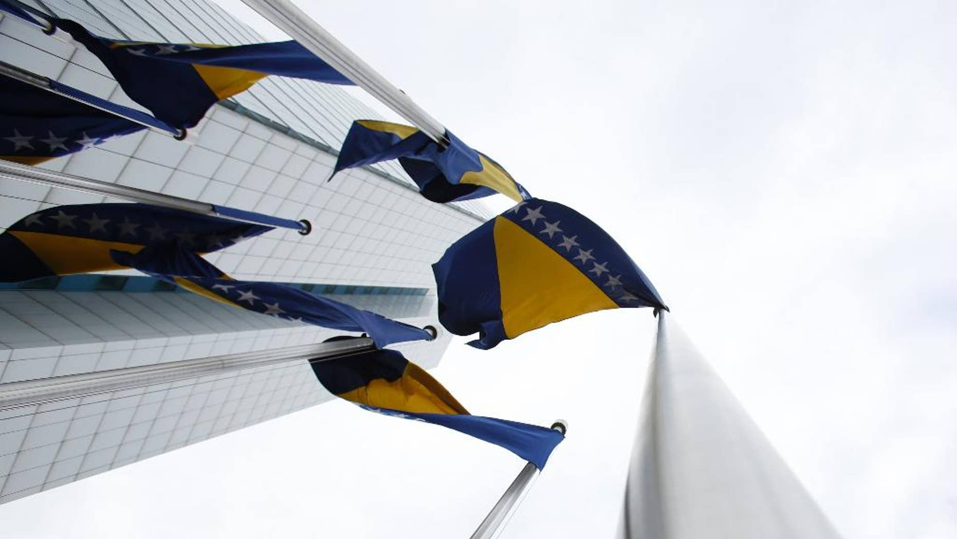 In this photo taken on Friday, Feb. 12, 2016 Bosnian flags flutter in the wind near government building in Sarajevo, Bosnia. The European Union said Tuesday, Sept. 20, 2016, it will examine whether Bosnia has what it takes to become a member as the bloc continues with plans to expand just months after Britain decided to leave. (AP Photo/Amel Emric)