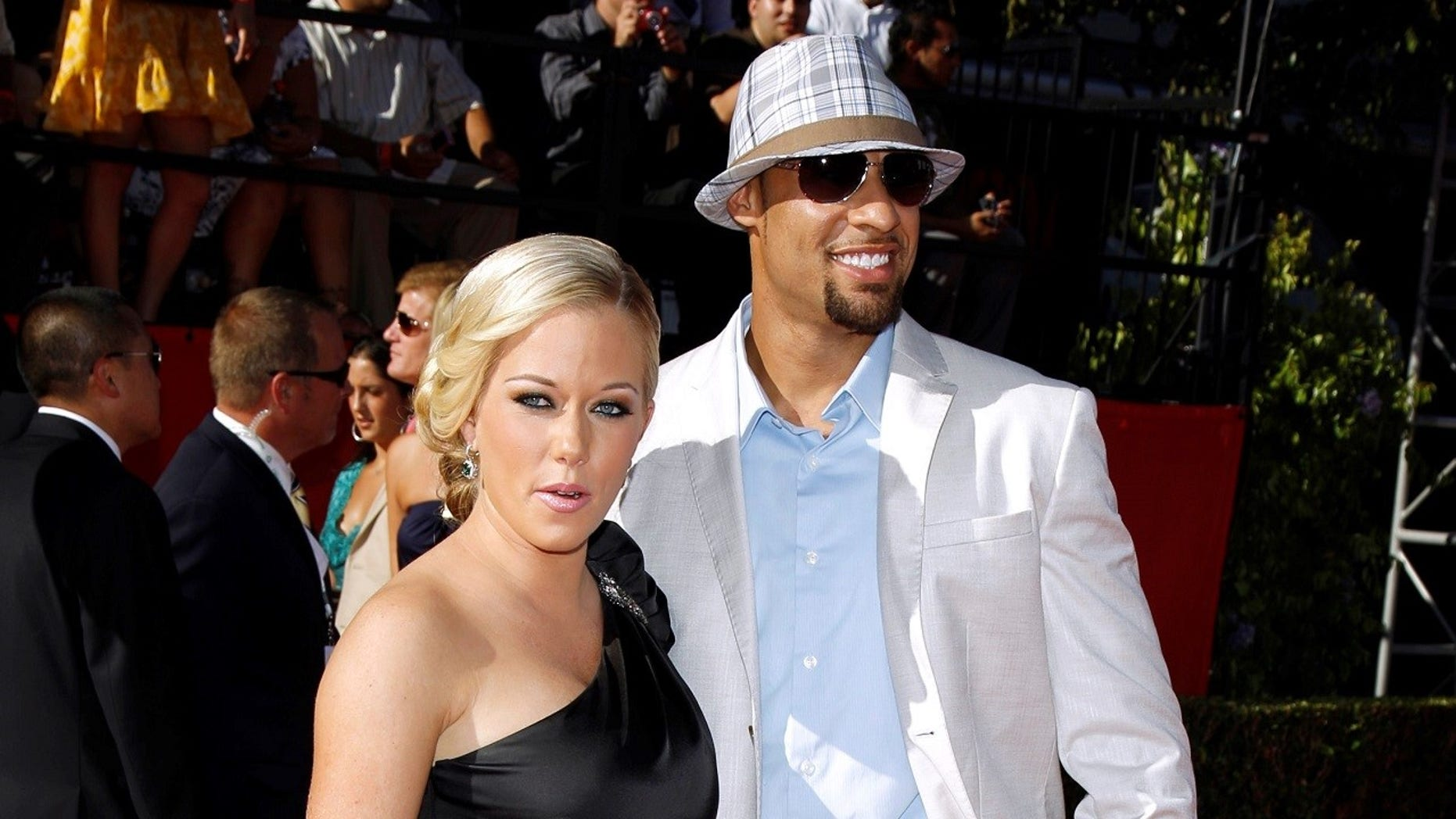 Kendra Wilkinson and Hank Baskett pose together in a 2009 photo. Wilkinson hinted she and Baskett are divorcing.