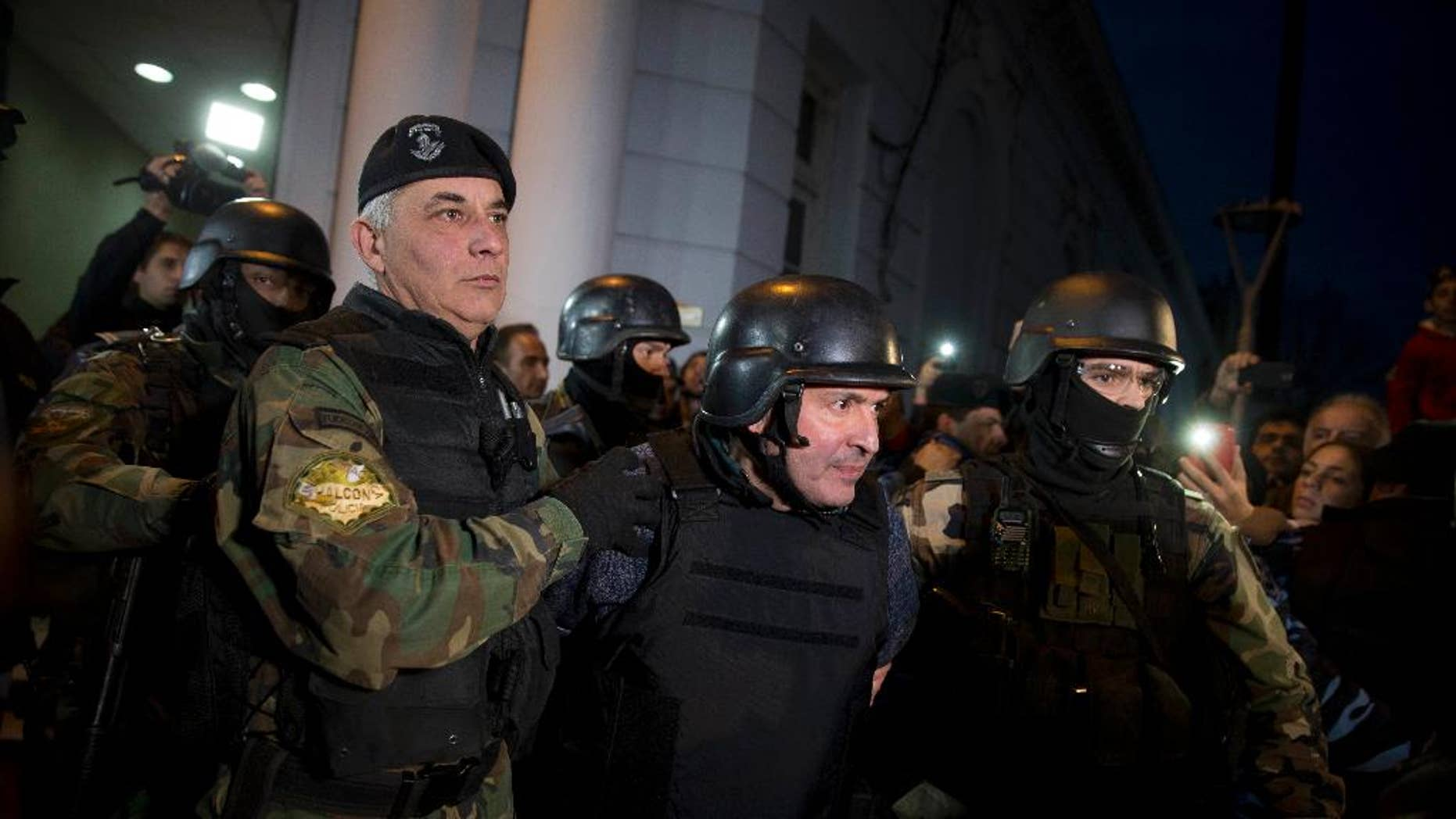 Former Public Works Secretary Jose Lopez, center, is escort by police outside the police station in the outskirts of Buenos Aires, Argentina, Tuesday, June 14, 2016. Lopez, an official in the former government of President Fernandez was arrested on Tuesday while trying to hide millions in cash and jewels in a monastery, captivating Argentina in what the cabinet chief said seems more like the plot of a Hollywood movie. (AP Photo/Natacha Pisarenko)
