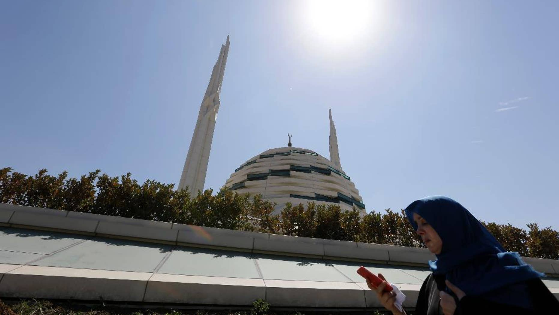 A woman checks her cell phone as she passes outside Marmara University Theological School mosque in Istanbul, Friday, Aug. 19, 2016. Turkey accuses U.S.-based cleric Fethullah Gulen of masterminding the July 15th coup and has launched a massive crackdown on his movement, detaining more than 40,000 people and dismissing tens of thousands from government jobs. (AP Photo/Thanassis Stavrakis)