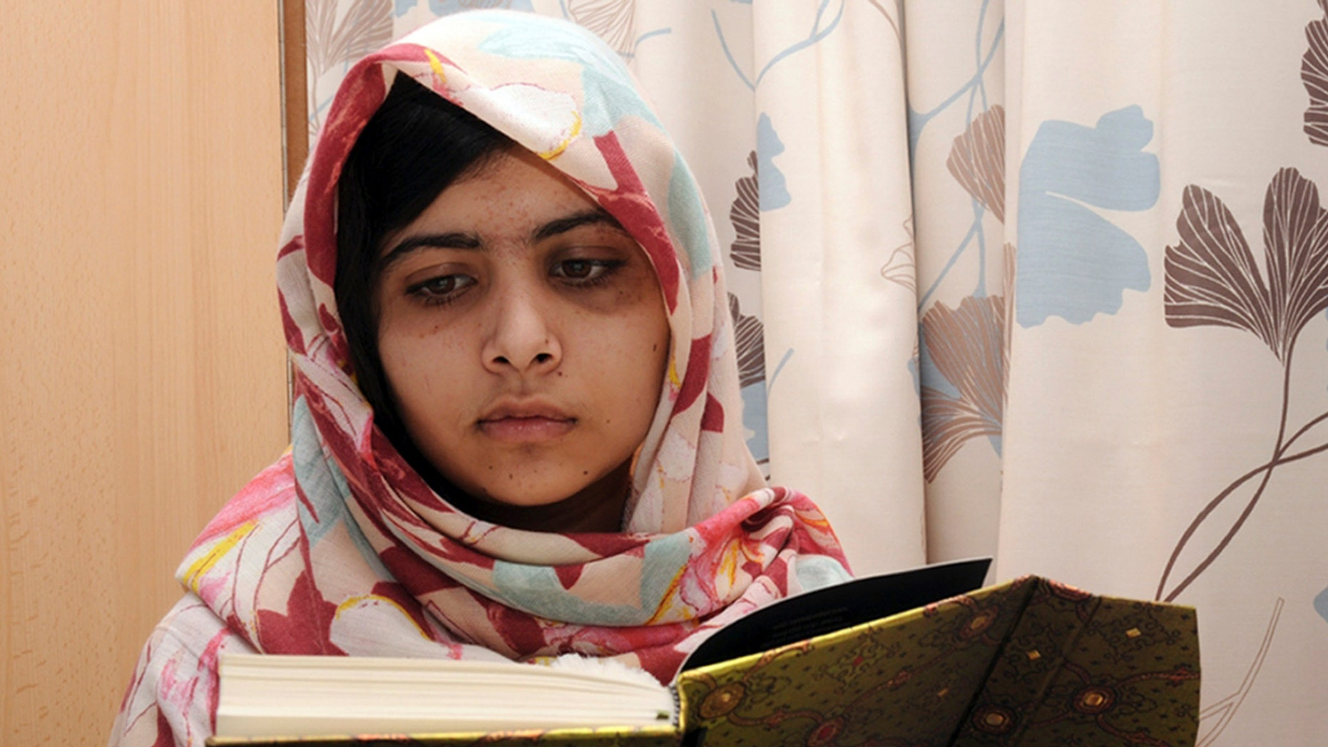 In this undated file photo provided by Queen Elizabeth Hospital in Birmingham, England, Malala Yousufzai, the 15-year-old girl who was shot at close range in the head by a Taliban gunman in Pakistan, reads a book as she continues her recovery at a hospital.
