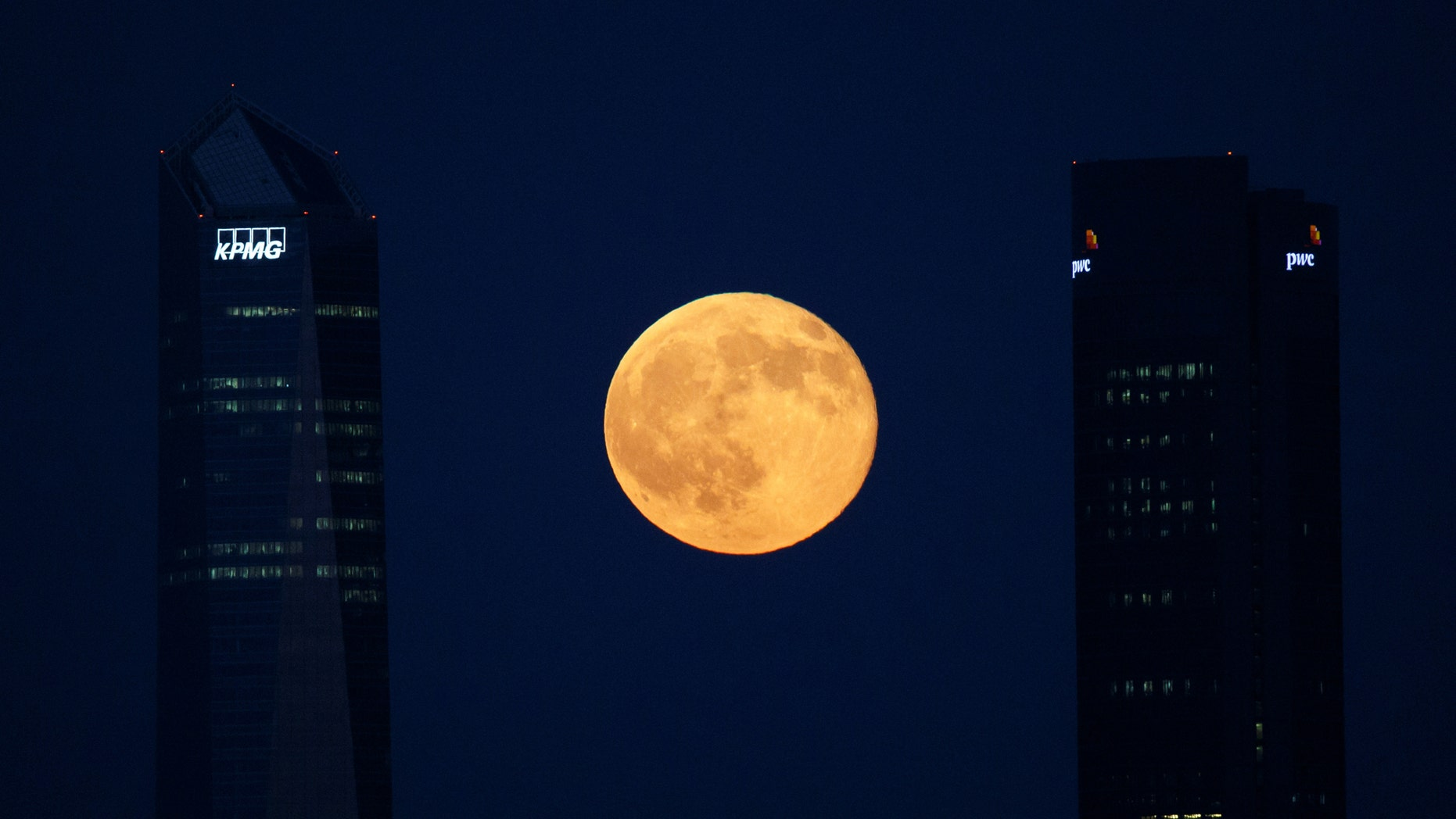 File photo: The full moon rises between buildings in the Four Towers business district in Madrid, Spain, July 9, 2017. (REUTERS/Paul Hanna)
