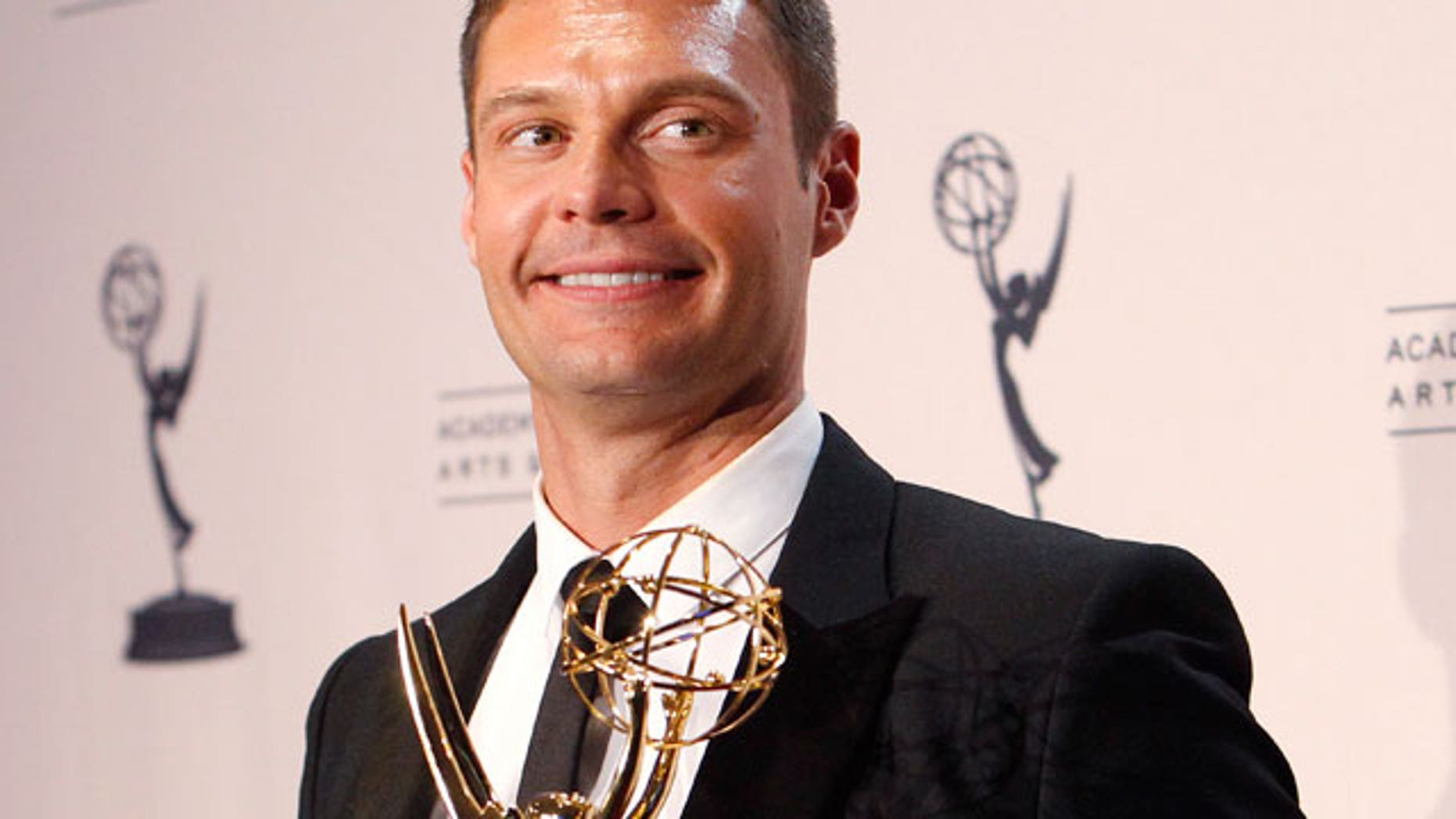 "Aug. 2010: Seacrest holds his Emmy award for Outstanding Reality Program for ""Jamie Oliver's Food Revolution"" in Los Angeles. (Reuters)"