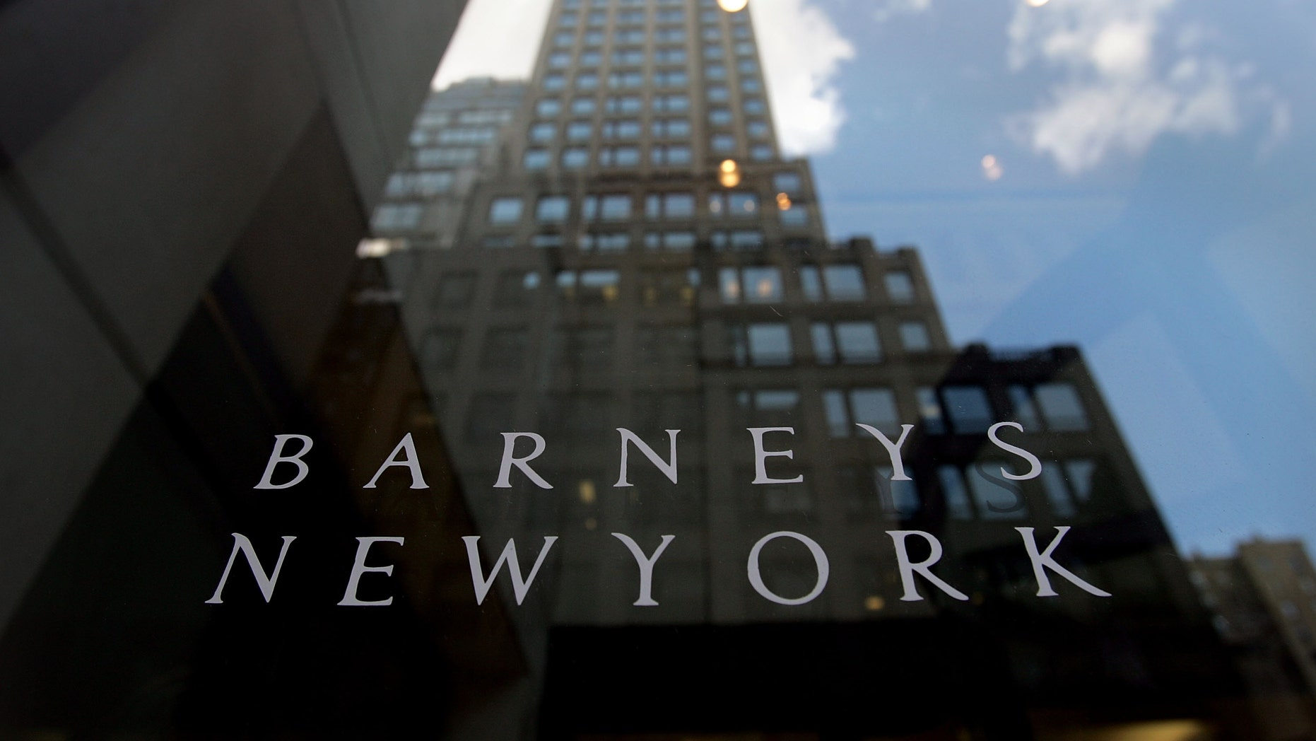 NEW YORK - JUNE 22: A building is reflected in the Barneys New York store window June 22, 2007 in New York City. Jones Apparel Group Inc. plans to sell Barneys New York to the Dubai investment firm Istithmar for $825 million.  (Photo by Mario Tama/Getty Images)