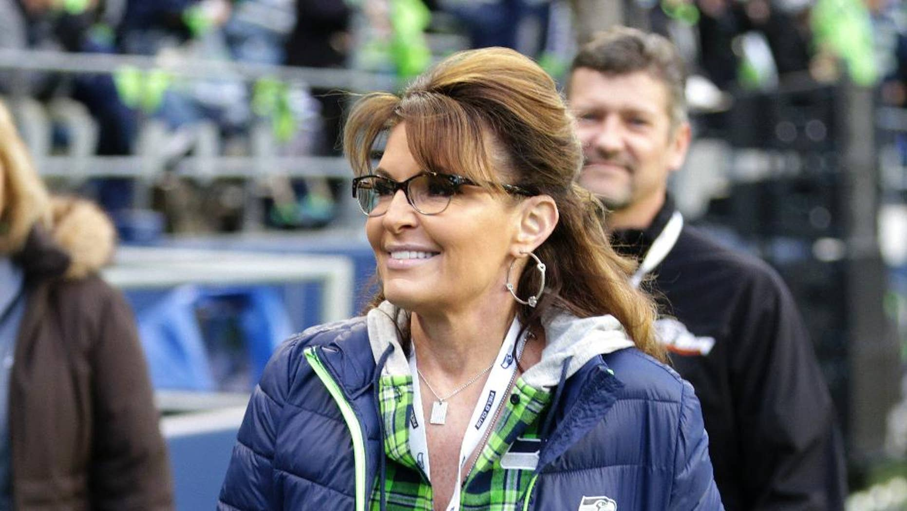 """FILE - In a Thursday, Dec. 15, 2016 file photo, Sarah Palin, political commentator and former governor of Alaska, walks on the sideline before an NFL football game between the Seattle Seahawks and the Los Angeles Rams, in Seattle. A story posted by Newslo on Jan. 6, 2017, claiming Palin blamed recent fatal shooting at a Florida airport on """"Mexican Muslims"""" is false. (AP Photo/Scott Eklund, File)"""