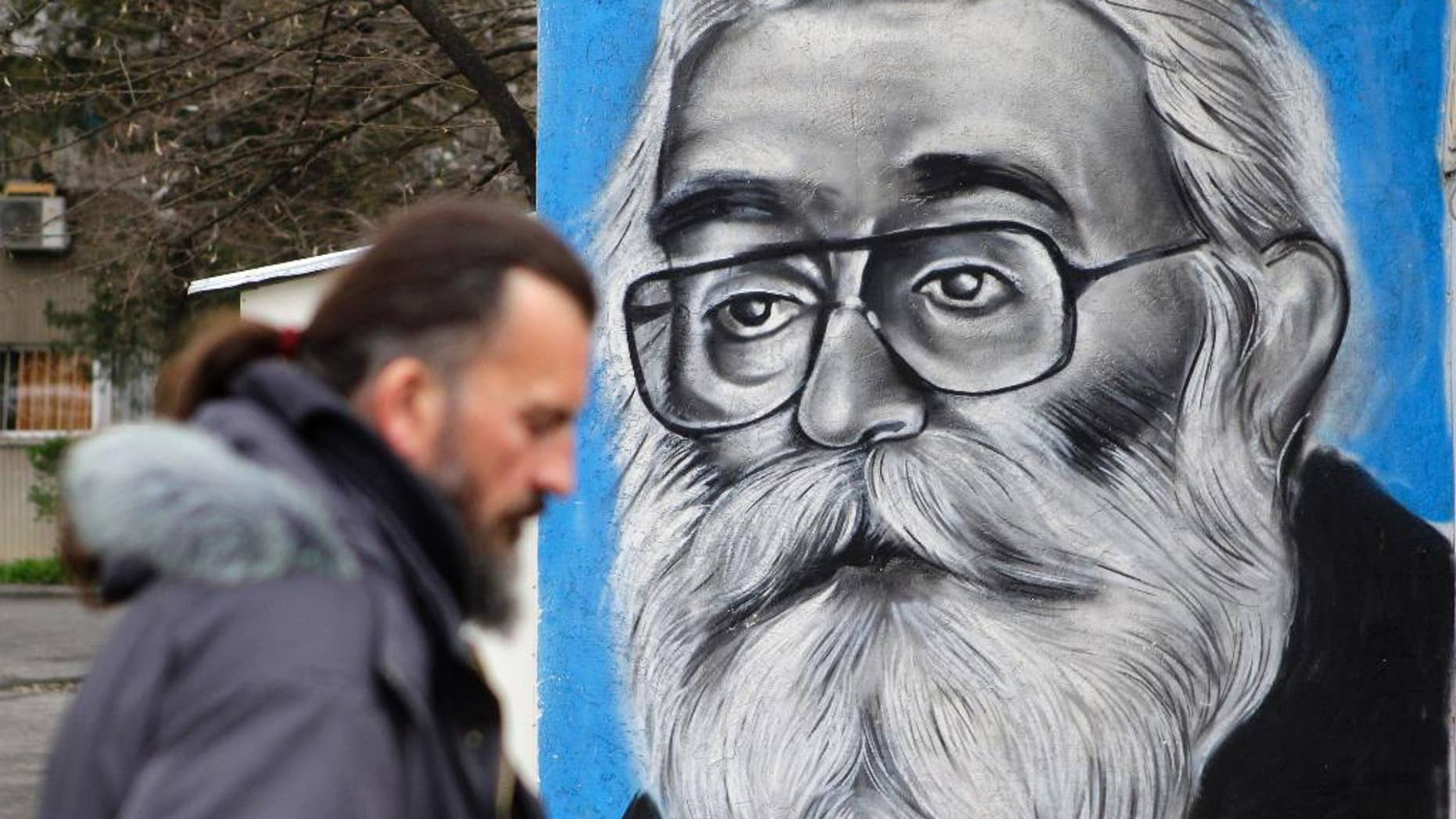 A man walks past a mural depicting Radovan Karadzic in Belgrade, Serbia, Thursday, March 24, 2016. A United Nations war crimes tribunal is passing judgment Thursday on former Bosnian Serb leader Radovan Karadzic, a landmark case against one of the alleged architects of Serb atrocities during Bosnia's 1992-95 war that left 100,000 dead. (AP Photo/Andrej Cukic)