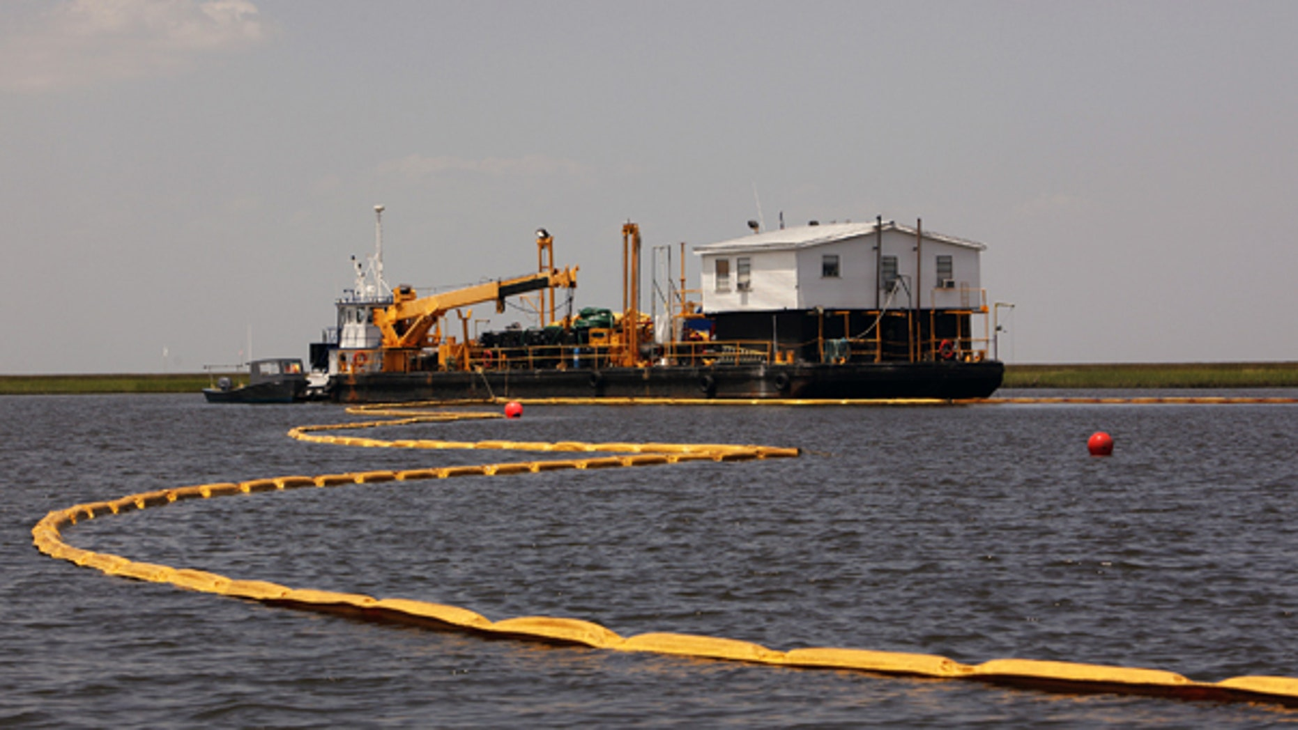 July 31: Oil containment boom is laid out in Treasure Pass, in waters near Yscloskey, La.