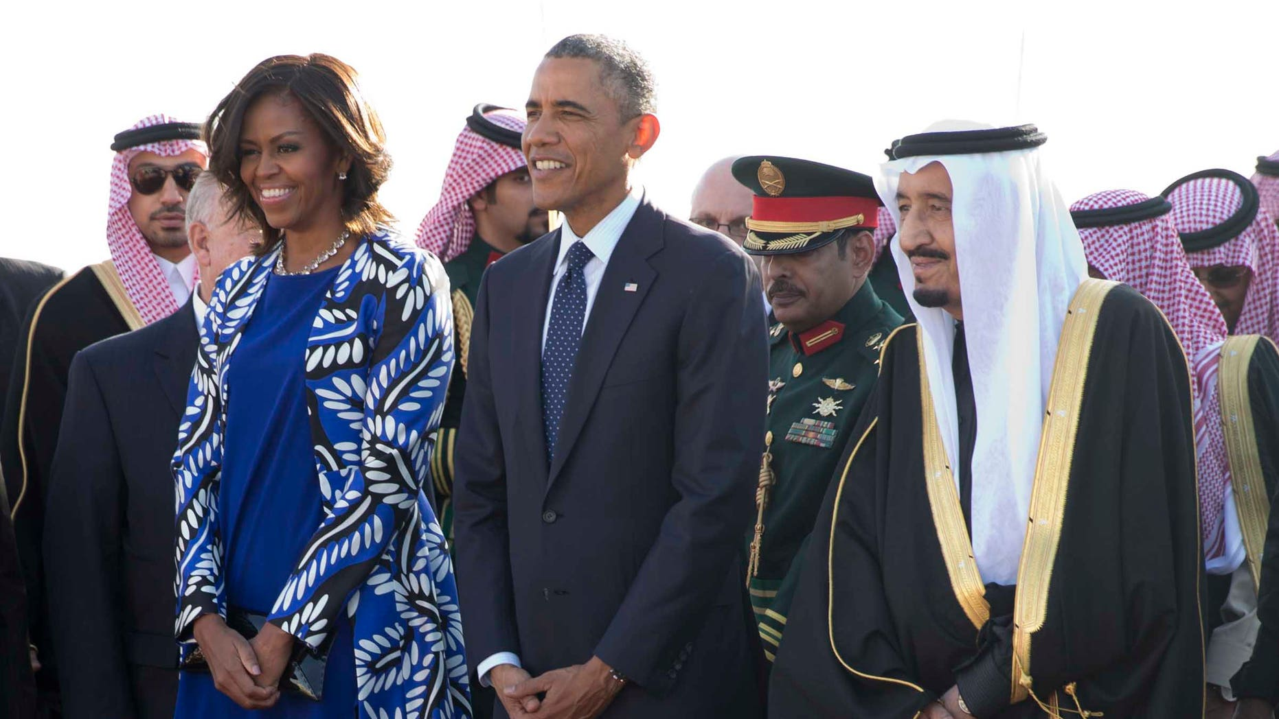 President Barack Obama and first lady Michelle Obama stand with new Saudi King Salman bin Abdul Aziz they arrive on Air Force One at King Khalid International Airport, in Riyadh, Saudi Arabia, Tuesday, Jan. 27, 2015. (AP Photo/Carolyn Kaster)