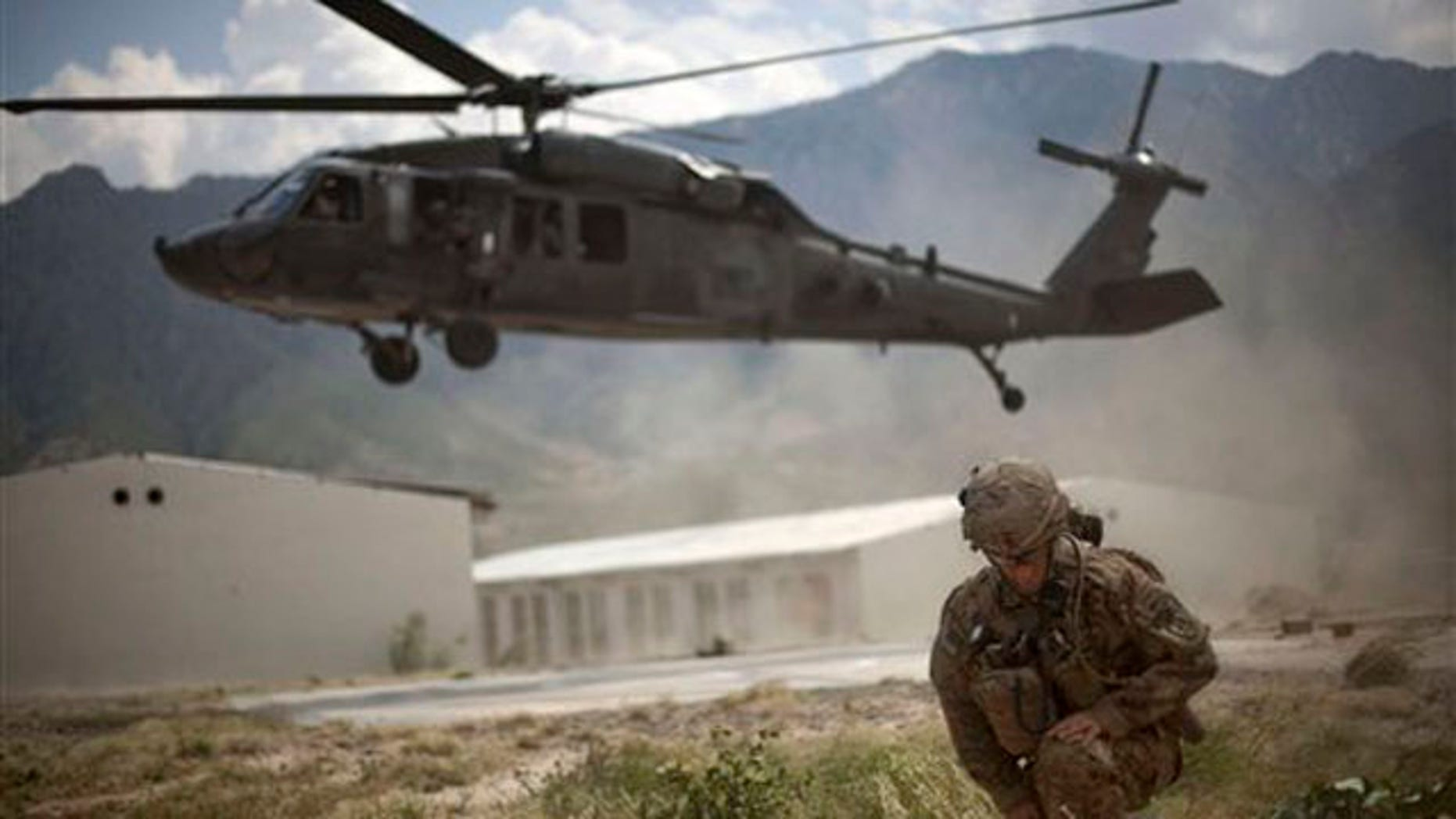In this Sept. 15, 2011, file photo a commanding officer of the U.S. Army turns from the rotor wash of a Blackhawk helicopter, following a key leader engagement at the Shigal district center in Kunar province, Afghanistan.