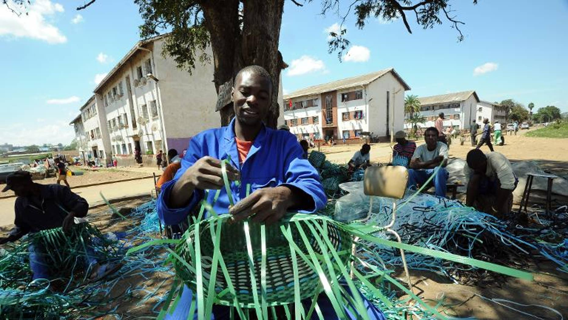 A man makes a basket with packaging strips in the Mbare suburb of Zimbabwe's capital Harare, on March 17, 2013