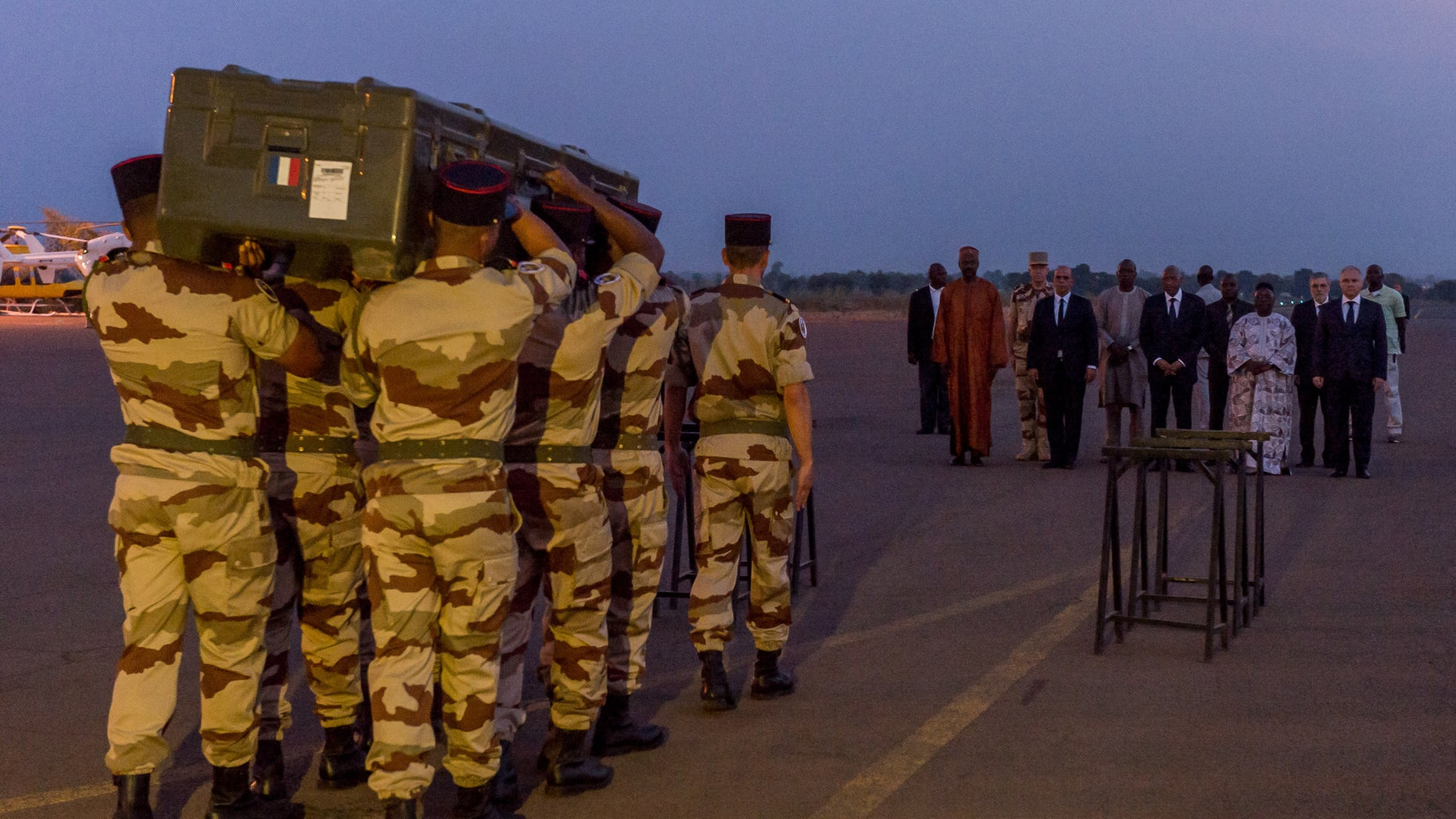 This photo taken and provided Sunday, Nov. 3, 2013, by the ECPAD or French army's image division, shows french soldiers carrying the casket of one of the two journalists executed in northern Mali, during a military ceremony of the removal of the bodies at Bamako military airport in Mali. The slayings of Ghislaine Dupont, 51, and Claude Verlon, 58, shocked France and underscored how insecure parts of northern Mali remain months after a French-led military intervention against al-Qaida and other extremists. (AP Photo/Gilles Gesquiere, ECPAD)