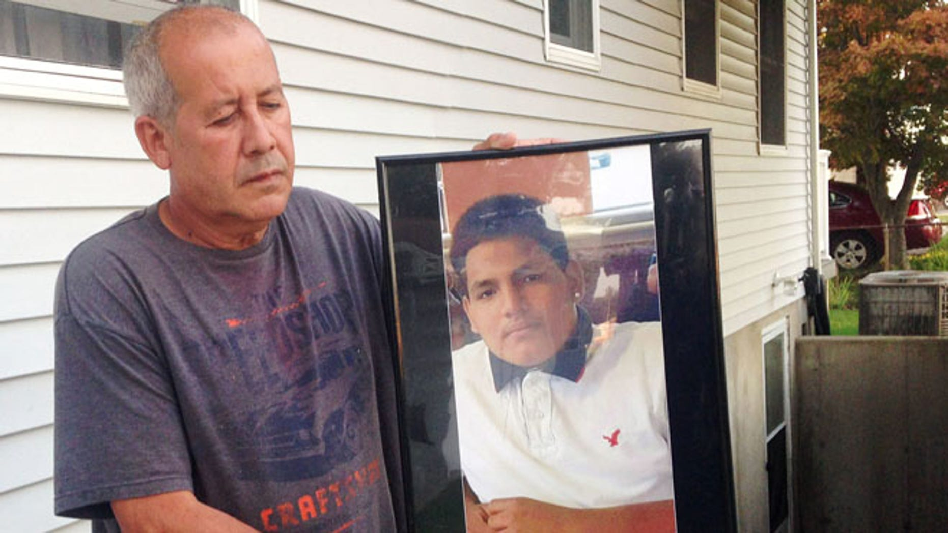Abraham Chaparro holds a photograph of his murdered stepson Miguel Garcia-Moran, outside his home in Brentwood, N.Y.