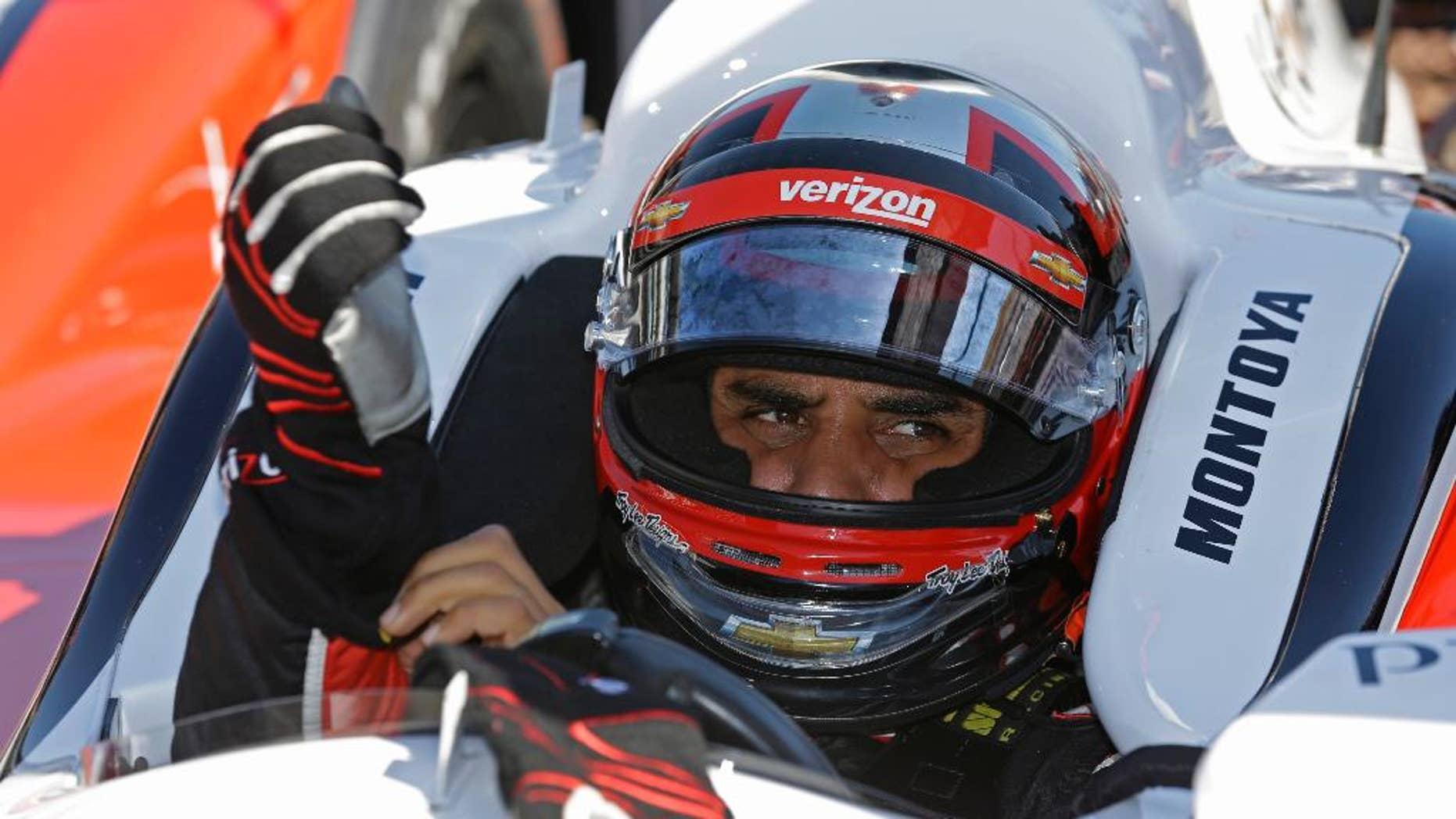 Juan Pablo Montoya, of Colombia, puts on his gloves as he prepares to drive on the final day of practice for the Indianapolis 500 IndyCar auto race at the Indianapolis Motor Speedway in Indianapolis, Friday, May 23, 2014. The 98th running of the Indianapolis 500 is Sunday. (AP Photo/Michael Conroy)