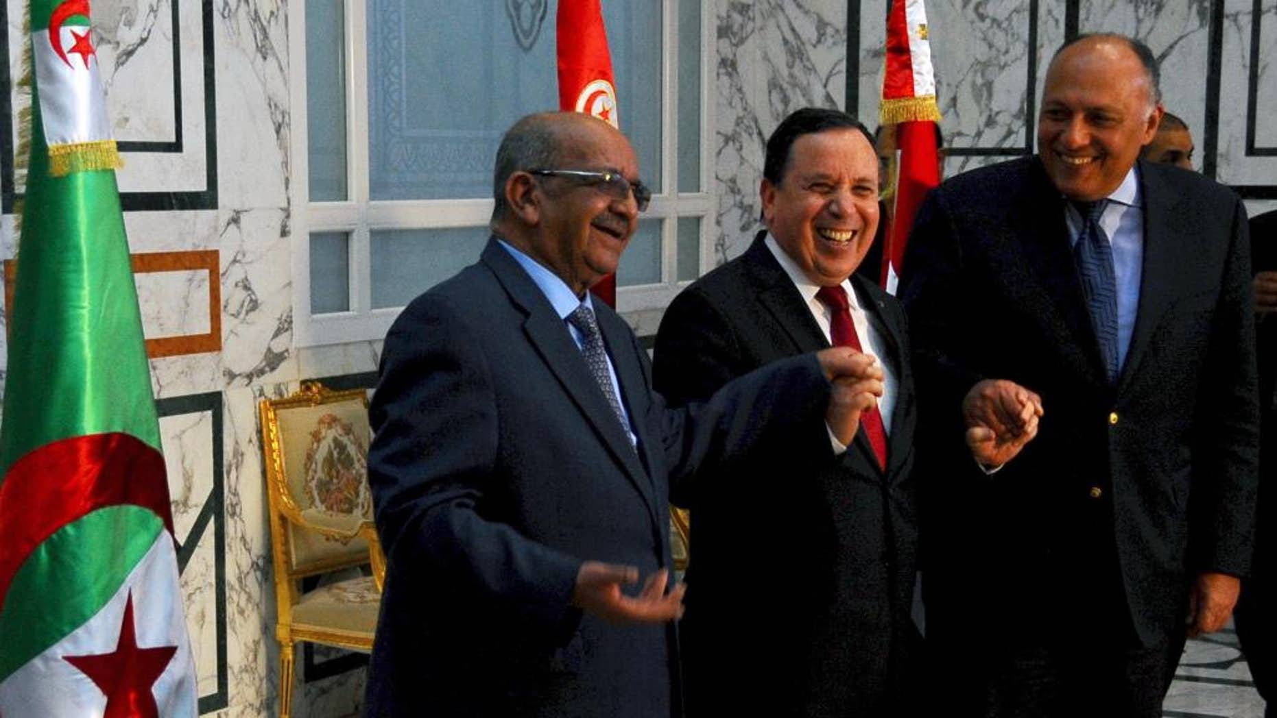 Tunisia Foreign Minister Khemaies Jhinaoui, center, shakes hands with his Egyptian counterpart Sameh Shoukry, right, and Algerian Minister of Maghreb Affairs, African Union and Arab League Abdelkader Messahel, prior to their meeting to discuss efforts to resolve the Libyan conflict in Tunis, Sunday, Feb. 19, 2017. (AP Photo/Hassene Dridi)