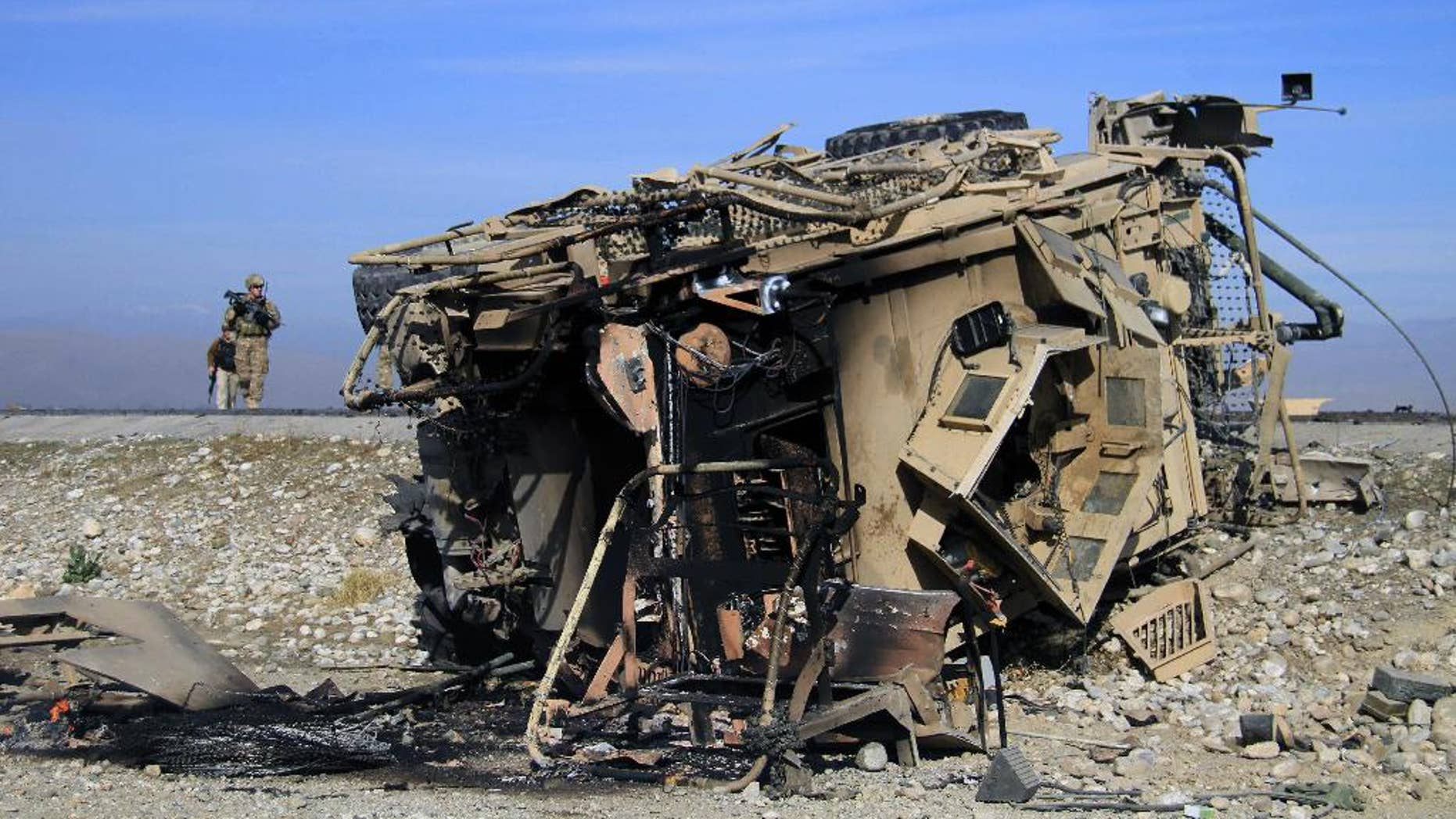 Nov. 13, 2014: A U.S. soldier inspects the site of a suicide attack targeting a foreign convey in Behsood district of Jalalabad east of Kabul