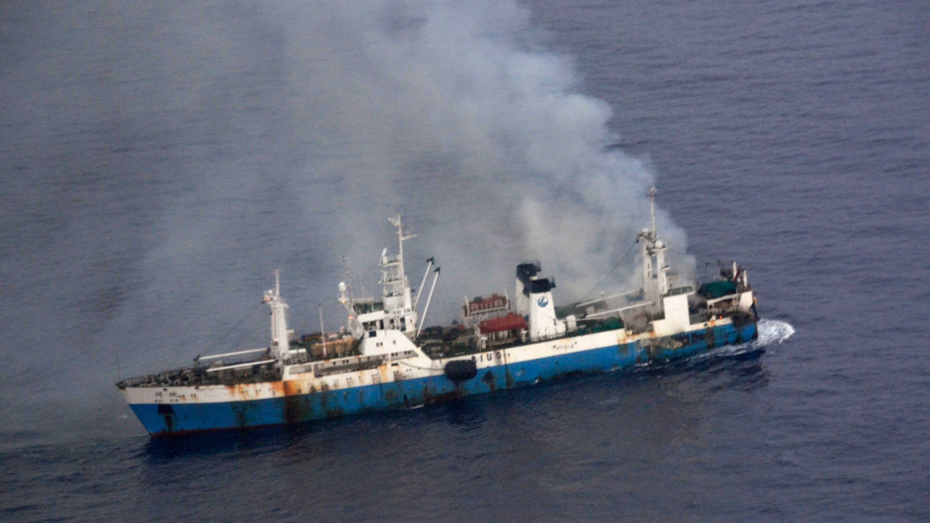 In this picture released by Chile's Air Force, smoke billows from a Chinese factory fishing ship Kai Xin just off the coast of Antarctica, Wednesday, April 17, 2013. Chilean authorities say around 90 crew members have been rescued from the burning ship by the crew of the Norwegian ship Juvel, and Chile's military says it's ready to intervene if necessary to prevent an ecological disaster. (AP Photo/Chile's Air Force)