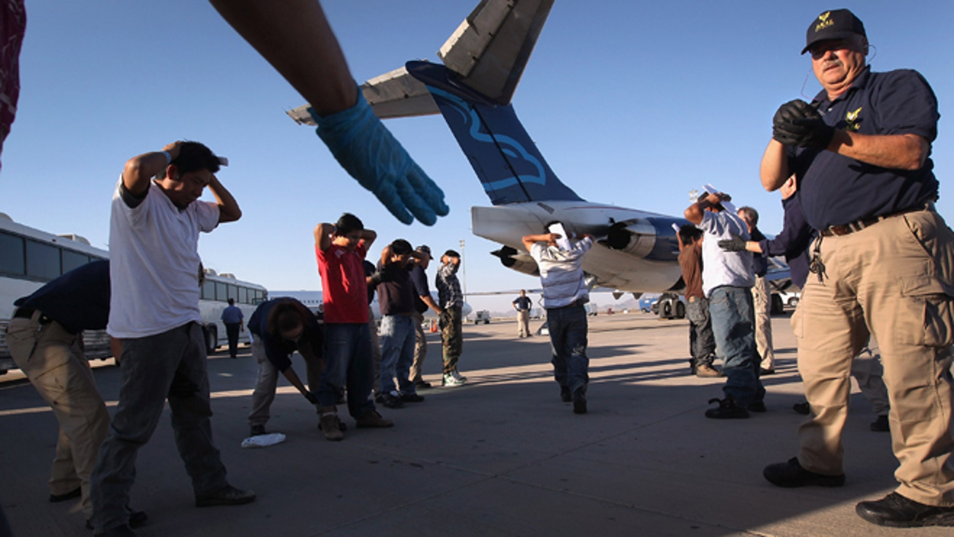 "MESA, AZ - JUNE 24:  Undocumented Guatemalan immigrants are body searched before boarding a deportation flight to Guatemala City, Guatemala at Phoenix-Mesa Gateway Airport on June 24, 2011 in Mesa, Arizona. The U.S. Immigration and Customs Enforcement agency, ICE, repatriates thousands of undocumented Guatemalans monthly, many of whom are caught in the controversial ""Secure Communities"" data-sharing program which puts local police on the frontlines of national immigration enforcement. ICE recently announced a set of adjustments to the federal program after many local communities and some states, including New York, insisted on opting out, saying immigrants were being deported for minor offenses such as traffic violations. Guatemala ranks only second to Mexico in the number of illegal immigrants deported from the United States.  (Photo by John Moore/Getty Images)"