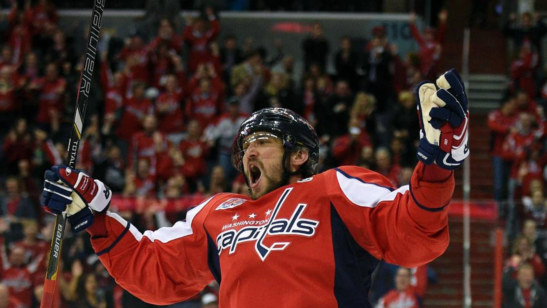 Washington Capitals left wing Alex Ovechkin (8), of Russia, celebrates his goal against the Carolina Hurricanes during the first period of an NHL hockey game, Tuesday, March 31, 2015, in Washington. It was Ovechkins' 50th goal of the year. (AP Photo/Nick Wass)