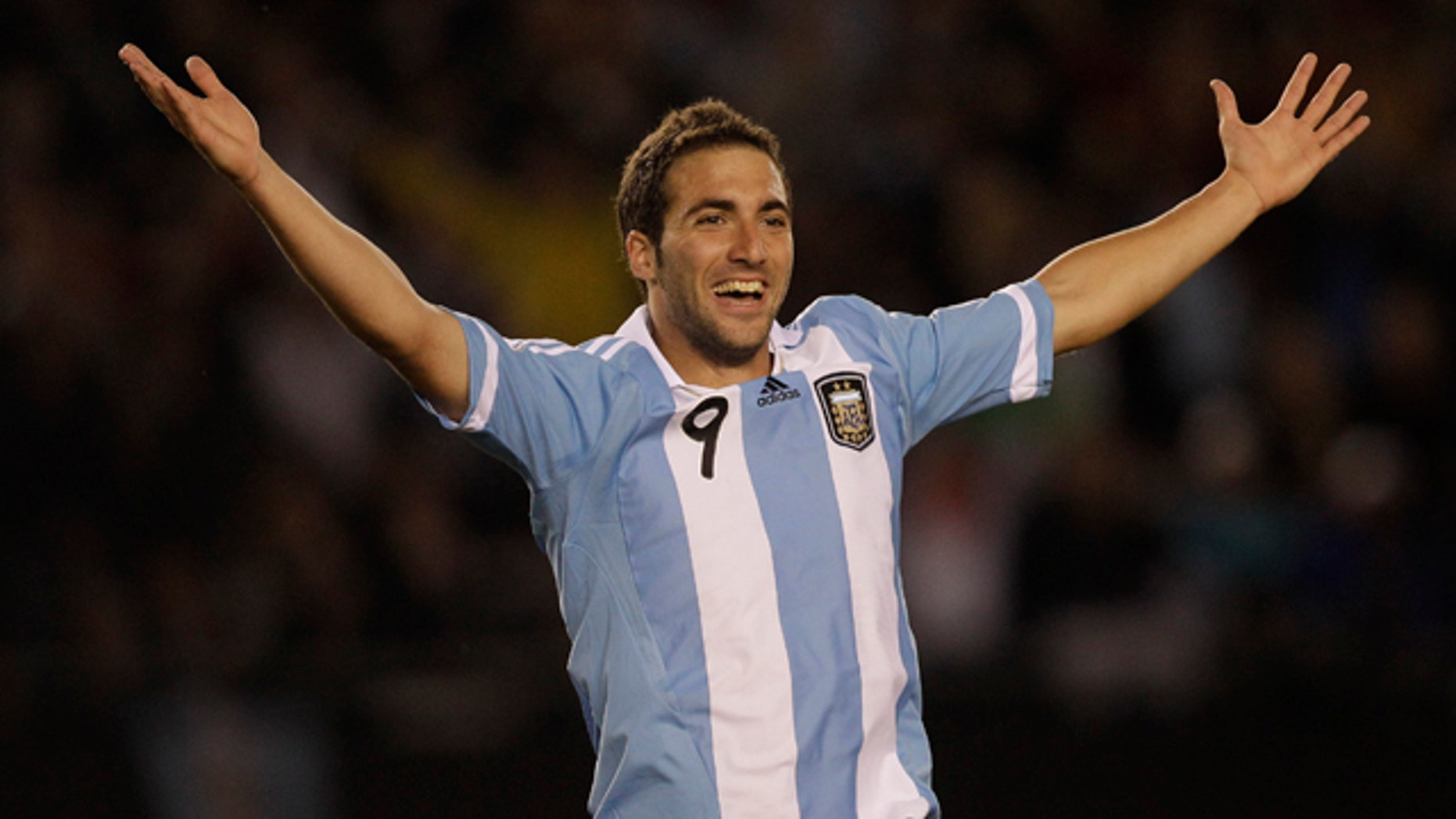 Argentina's Gonzalo Higuain celebrates after scoring his team's third goal during a World Cup 2014 qualifying soccer game against Chile in Buenos Aires, Argentina,  Friday, Oct. 7, 2011. (AP Photo/Eduardo Di Baia)