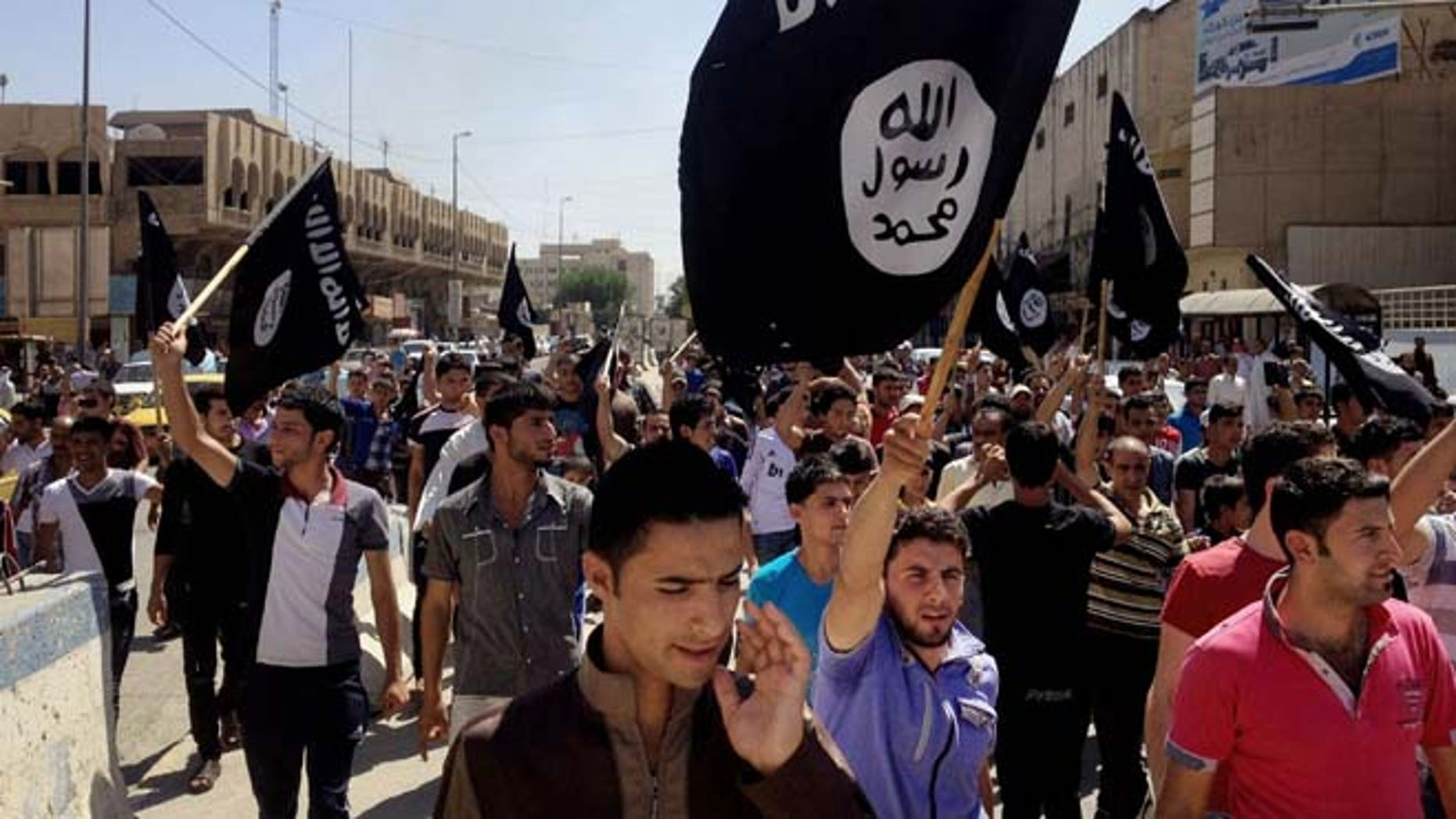 June 16, 2014: Demonstrators chant pro-Islamic State group slogans as they carry the group's flags in front of the provincial government headquarters in Mosul, 225 miles northwest of Baghdad.
