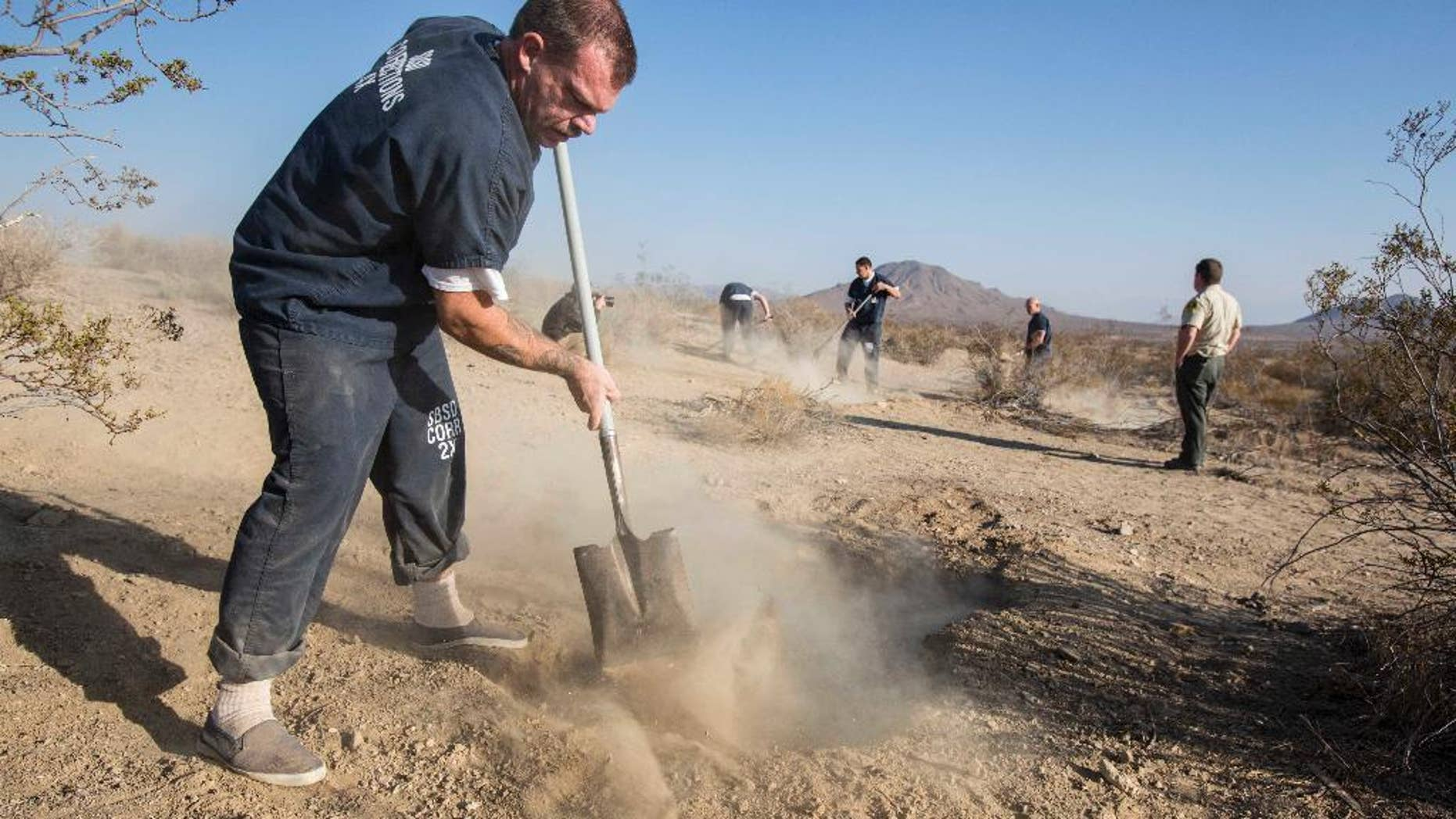 FILE - In this Nov. 15, 2013 file photo, workers fill the two shallow graves at the site on the outskirts of Victorville that contained the skeletal remains of members of missing McStay family in San Bernardino, Calif. Police investigating a missing persons report found a tall lamp lying on a bedroom floor and open suitcases containing folded clothes in the walk-in closet of a California home, according to court records unsealed Friday, Jan. 23, 2015, in the investigation that eventually led to the discovery of four dead family members in shallow desert graves. The documents offer the most detailed look yet of the disheveled condition of the family's house in Fallbrook, Calif., when investigators arrived in February 2010 while searching for Joseph McStay, then 40, his wife Summer, 43, and their two sons, Gianni, 4, and Joseph Jr., 3.(AP Photo/Ringo H.W. Chiu, File)