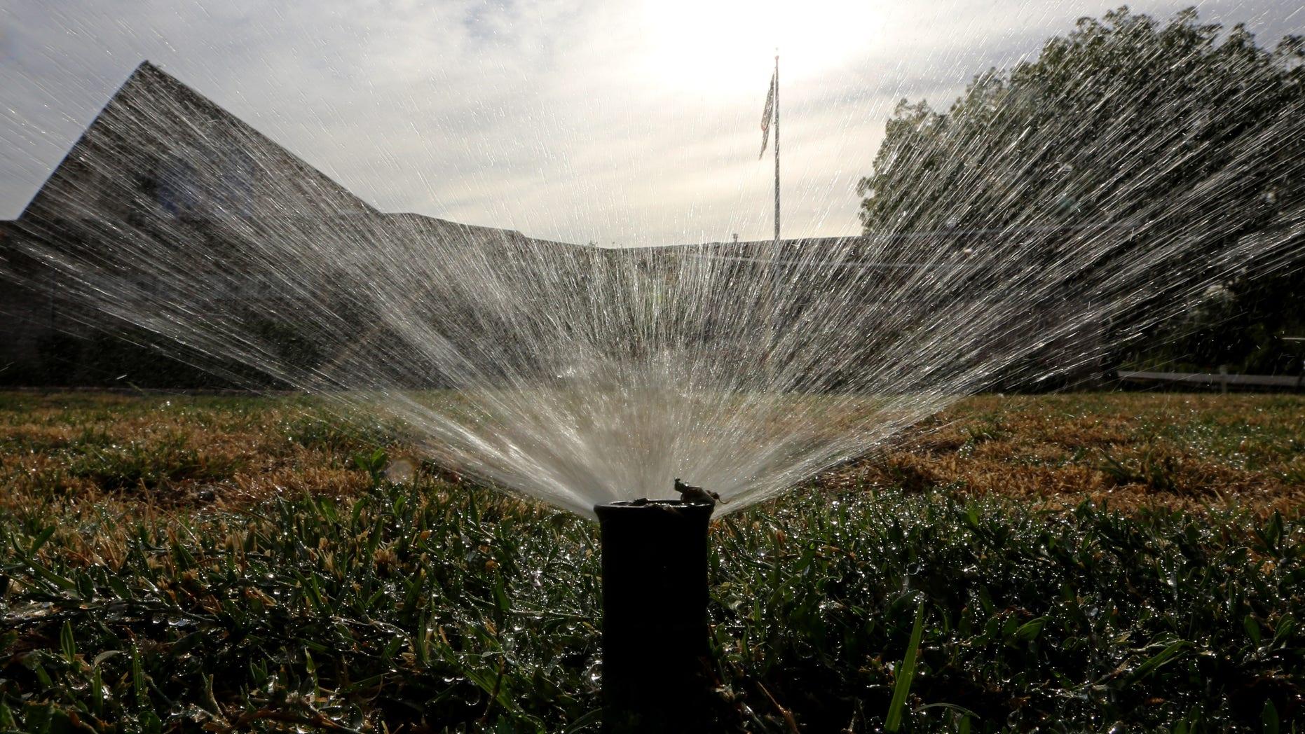 FILE -- Sprinklers water a lawn in Sacramento, Calif.