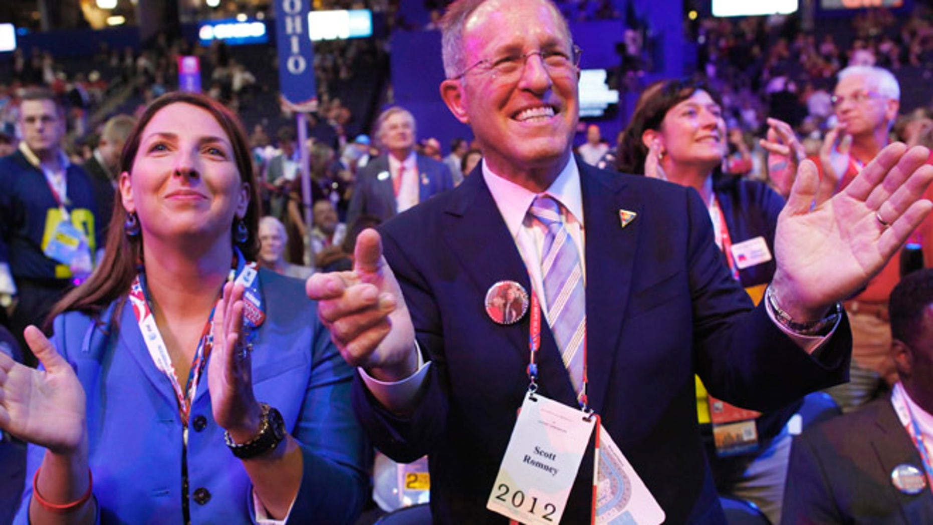 August 28, 2012: Scott Romney, brother of Republican presidential candidate Mitt Romney, applauds with his daughter Ronna during the second day of the Republican National Convention in Tampa, Florida.