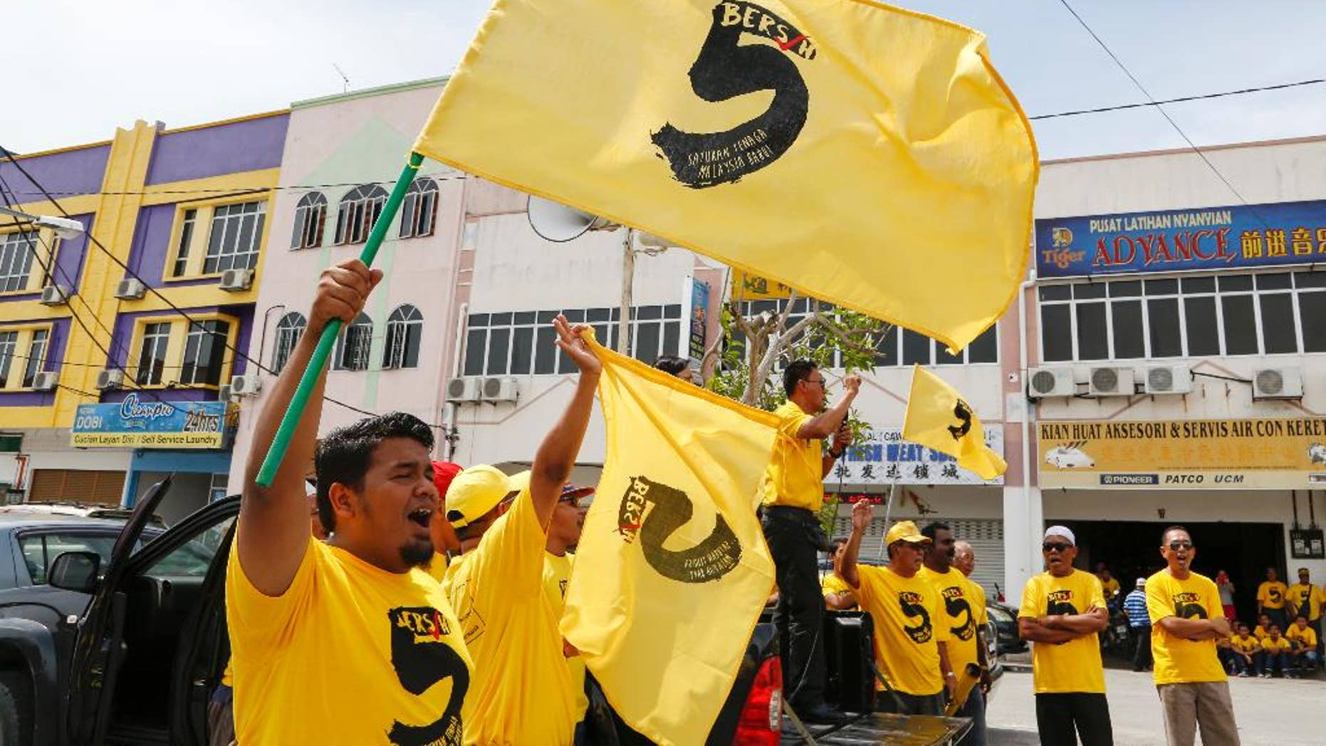 """In this Oct. 15, 2016 photo, pro-democracy activists wave """"Bersih 5"""" flags in Sekinchan, Malaysia. Malaysian pro-democracy activists have vowed to go ahead with a massive rally on Saturday, Nov. 19 to demand Prime Minister Najib Razak's resignation over a financial scandal despite a police ban and fears of clashes with a pro-government group. Chairwoman Maria Chin of Bersih says Saturday's rally in downtown Kuala Lumpur will protest poor governance and a lack of accountability that have led to """"grand corruption"""" in the 1MDB fund. (AP Photo/Lim Huey Teng)"""