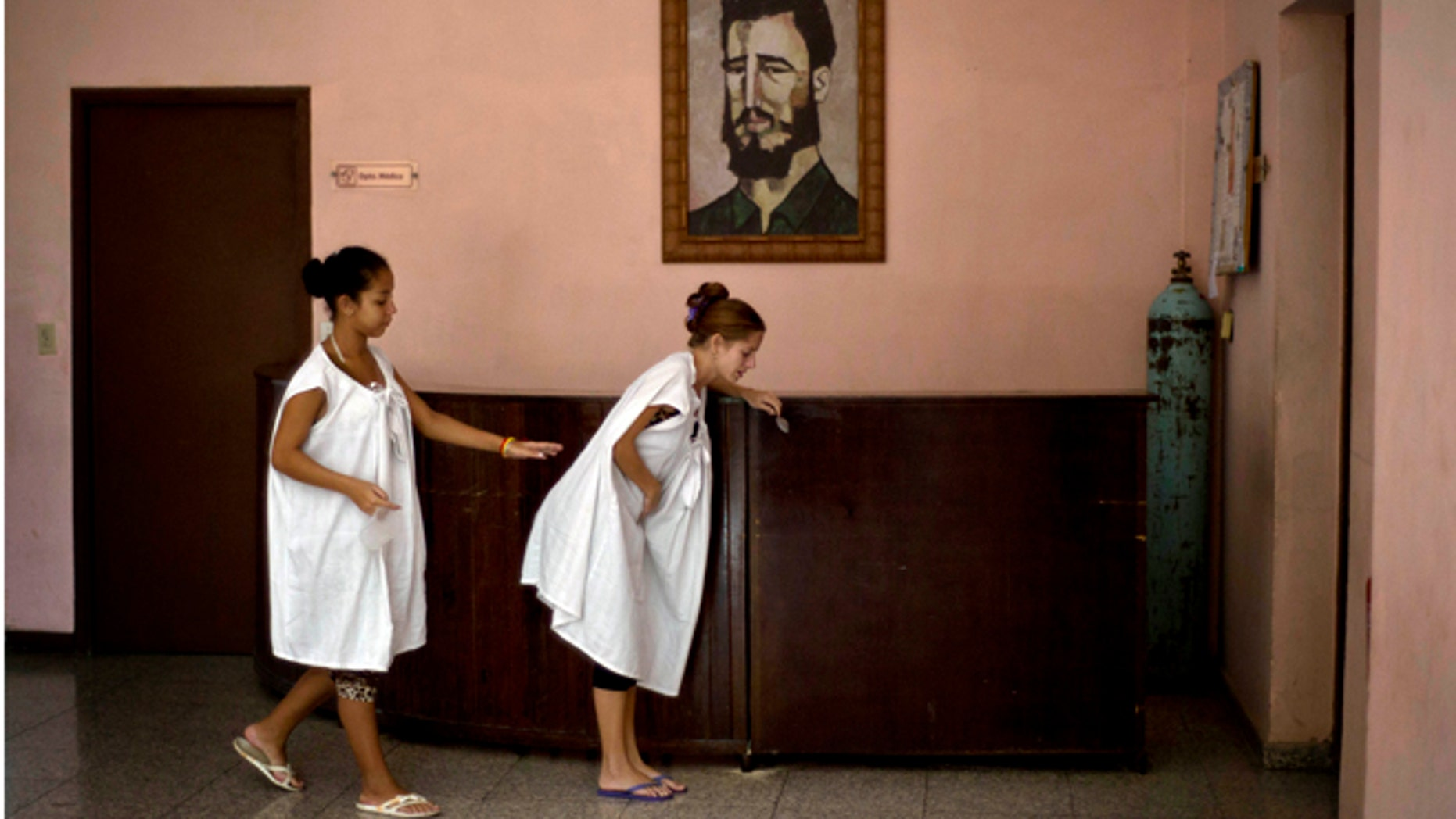 In this Oct. 27, 2014 photo, a pregnant woman is helped by another as she suffers from labor pains, while walking in front of a painting of Fidel Castro at a special maternity unit for high-risk pregnancies in Havana, Cuba. The island nation is in the midst of a broad campaign to drive up a birth rate that has fallen to the lowest in Latin America after years of fewer births, that mean that the number of working-age people in Cuba is expected to shrink starting next year, terrible news for an island attempting to jumpstart its stagnant centrally planned economy. (AP Photo/Ramon Espinosa)