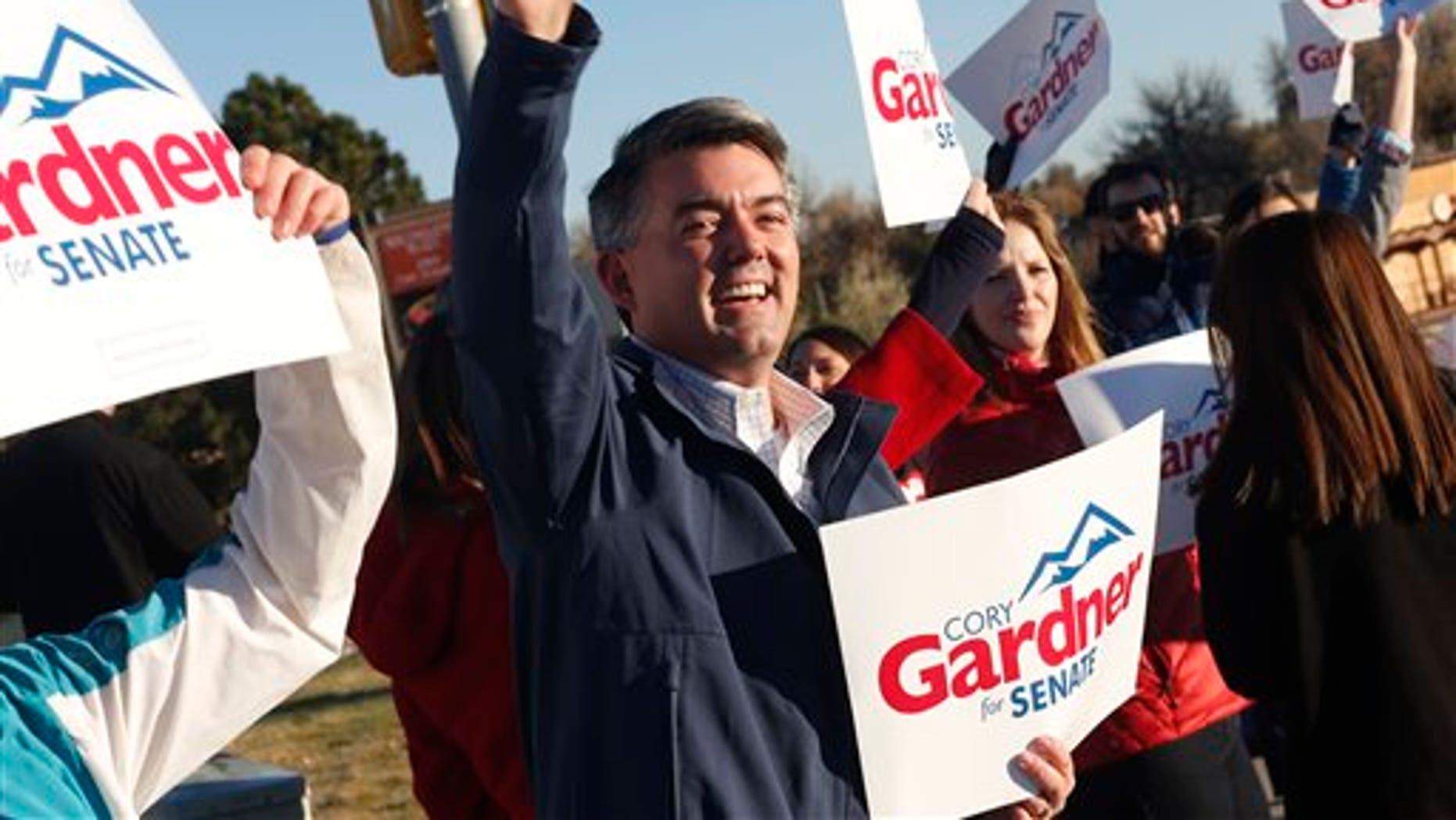Cory Gardner, Republican candidate for the U.S. Senate seat in Colorado, joins supporters in waving placards on corner of major intersection in south Denver suburb of Centennial, Colo., early on Tuesday, Nov. 4, 2014. Gardner is facing Democratic incumbent U.S. Sen. Mark Udall in a pitched battle for the seat. (AP Photo/David Zalubowski)