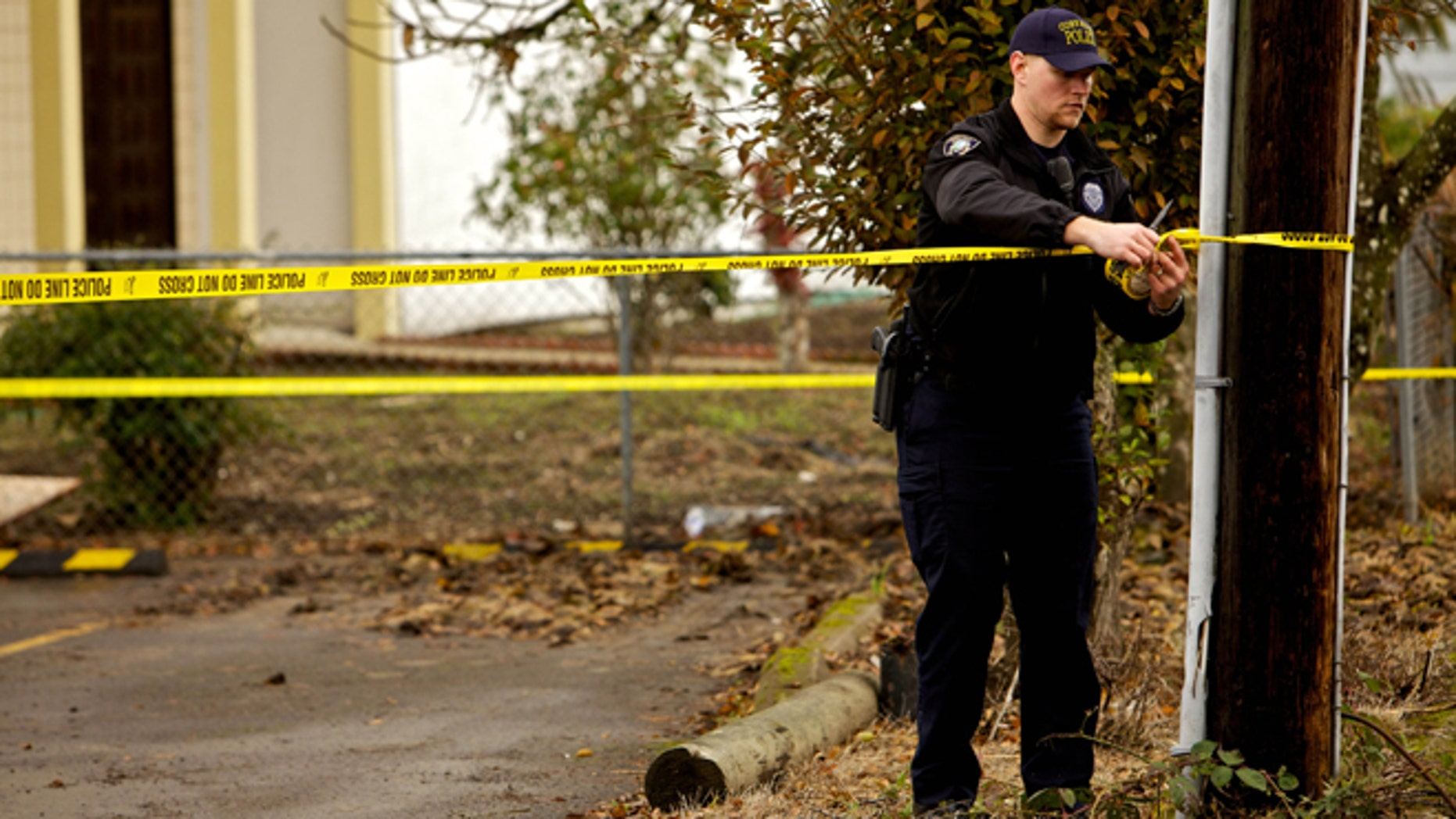 CORVALLIS, OR - NOVEMBER 28: A Corvallis police officer puts up police tape in front of the Salman Al Farisi Islamic Center on November 28, 2010 in Corvallis, Oregon. An arsonist set fire to the prayer center, which was sometimes attended by suspected Portland car bomber Mohamed Osman Mohamud. Mohamud, a Somali-born teenager, was arrested and charged with attempted use of a weapon of mass destruction when  he allegedly attempted to set off a car bomb during Christmas tree lighting ceremony in Pioneer Courthouse Square in Portland, Oregon. It was reported that civilians were not at risk because the bomb was supplied to him by undercover federal agents and the explosives were inert.   (Photo by Craig Mitchelldyer/Getty Images)
