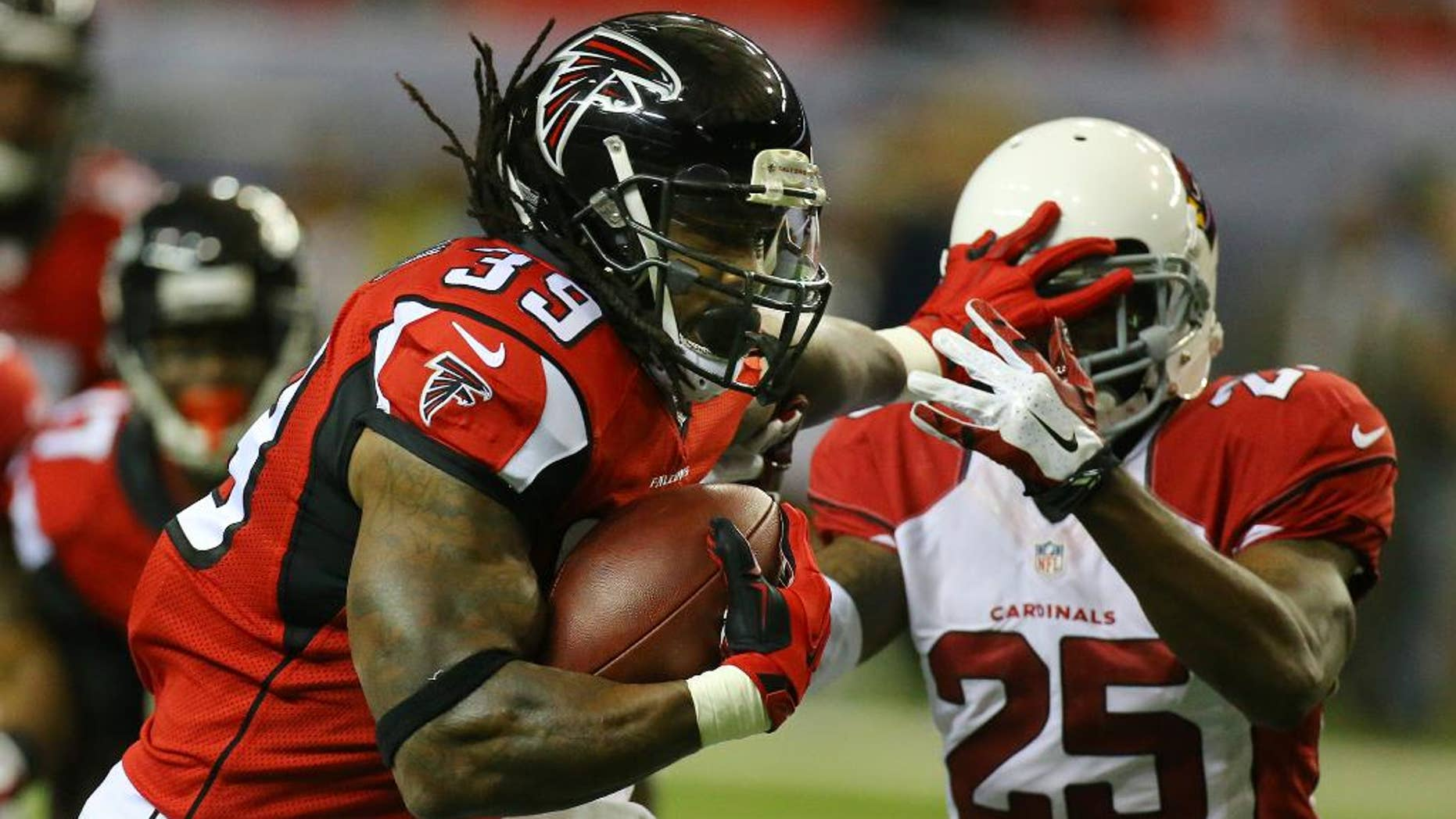 Falcons running back Steven Jackson stiff arms Cardinals Jerraud Powers breaking away for a 50-plus yard run setting up a Falcons touchdown on the opening drive during the first quarter in an NFL football game on Sunday, Nov. 30, 2014, in Atlanta. (AP Photo/Atlanta Journal-Constitution, Curtis Compton)