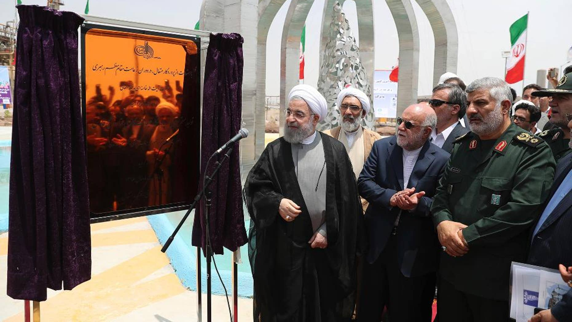 In this photo released by an official website of the office of the Iranian Presidency Sunday, April 30, 2017, Iranian President Hassan Rouhani, center left, inaugurates a new refinery that produces some 12 million liters (3.17 million gallons) of gas in its first phase, in Bandar Abbas, some 750 miles (1,205 kilometers) south of Tehran, Iran. Iran's official IRNA news agency is saying the country has become self-sufficient in producing the amount of gas the country requires on a daily basis. (Iranian Presidency Office via AP)