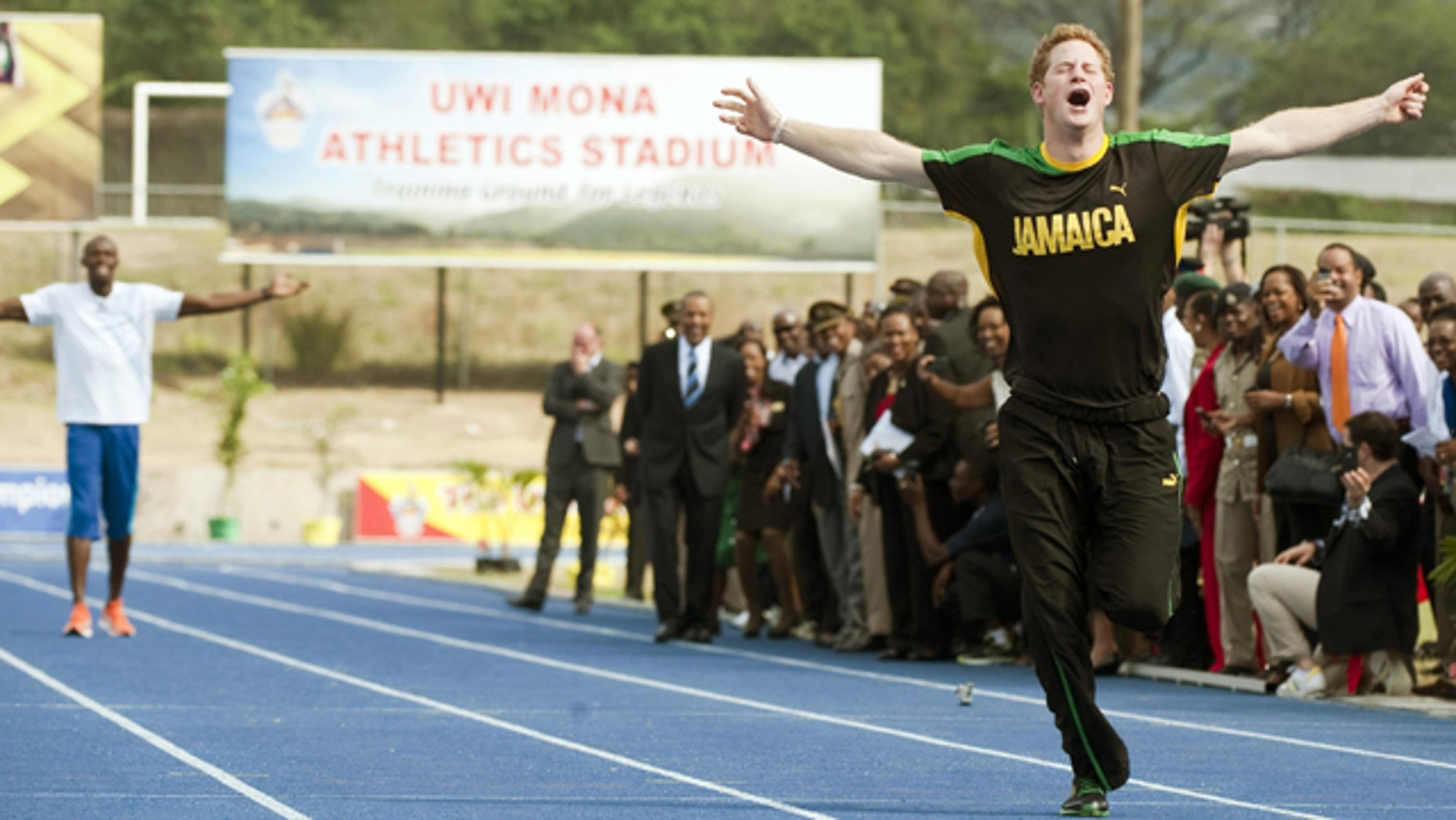 March 6: Prince Harry wins against Olympic sprint champion Usain Bolt, seen rear, by making a false start at a mock race at the University of the West Indies, in Jamaica.