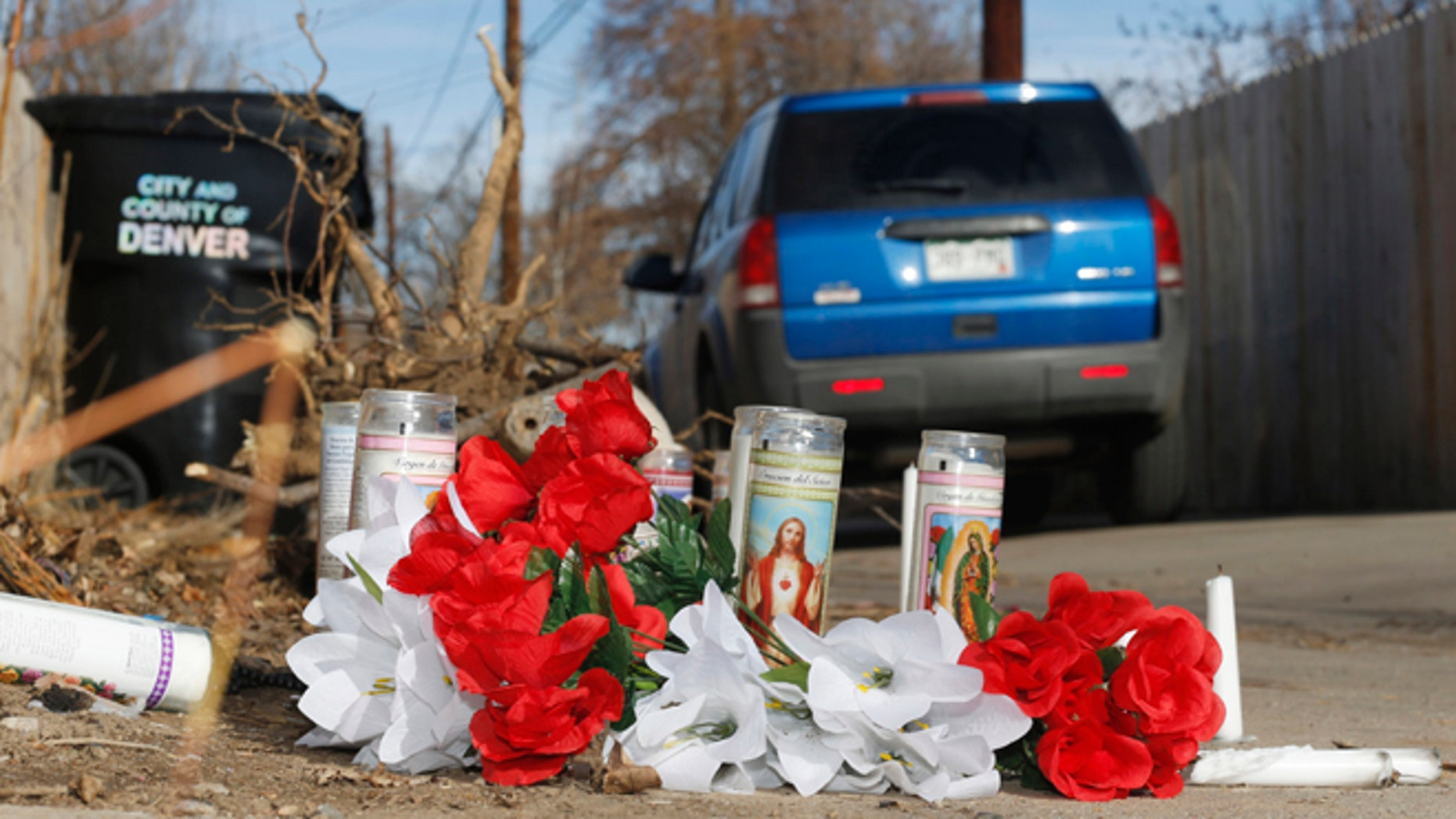 File--In this file photograph taken Tuesday, Jan. 27, 2015, a vehicle passes by the candles and bouquets left near the scene of a fatal police shooting in an alleyway in northeast Denver. A 17-year-old woman was fatally shot by police after she allegedly hit and injured an officer while driving a stolen vehicle early Monday, Jan. 26, in a northeast Denver alleyway. On Friday, June 5, 2015, Denver District Attorney Mitch Morrissey issued a statement saying that the two Denver Police officers involved in the shooting will not face criminal charges. (AP Photo/David Zalubowski, file)