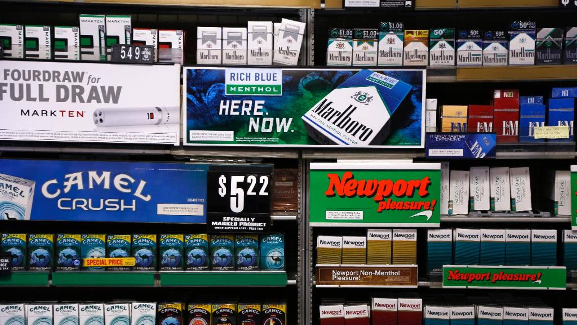 FILE - In this Friday, July 17, 2015 file photo, Camel and Newport cigarettes, both Reynolds American brands, are on display at a Smoker Friendly shop in Pittsburgh. British American Tobacco offered Friday, Oct. 21 2016 to buy Reynolds American Inc. in a $47 billion cash-and-stock deal that would create the world's largest publicly traded tobacco company and bring together brands like Camel, Dunhill, and Newport. The logic of the deal, analysts say, is to make up for a decline in the number of smokers in their home markets of the U.S. and Britain as they look to developing markets and new products, such as electronic cigarettes. (AP Photo/Gene J. Puskar, file)