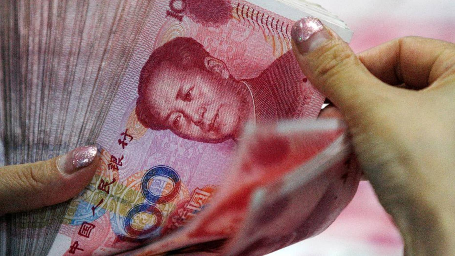 In this Tuesday, Aug. 11, 2015 photo, a bank clerk counts Chinese currency notes at a bank outlet in Huaibei in central China's Anhui province.  China's unexpected devaluation of its currency in August raised fears that the world's second-largest economy was slowing more than anyone had thought. (Chinatopix via AP, File) CHINA OUT