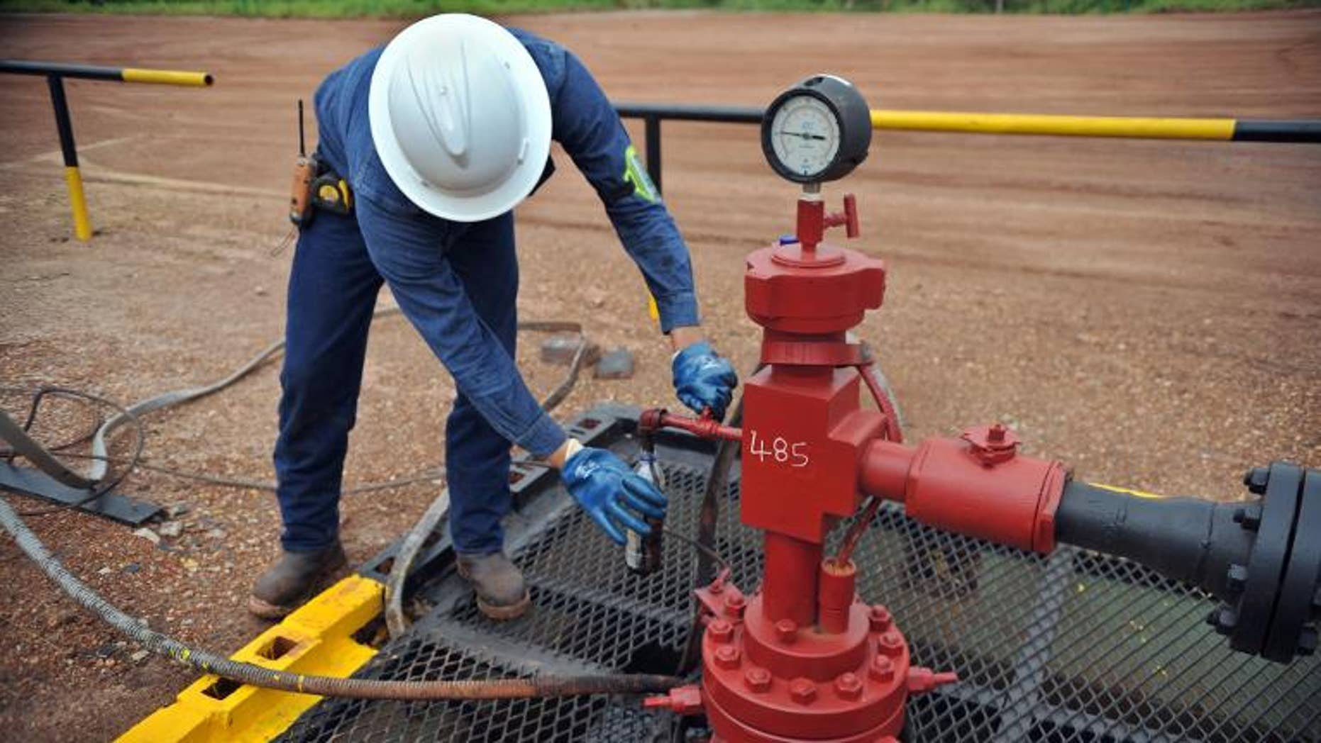 An engineer of Canadian oil company Pacific Rubiales takes a sample of heavy crude oil in Colombia's main oilfield Rubiales, on August 27, 2013