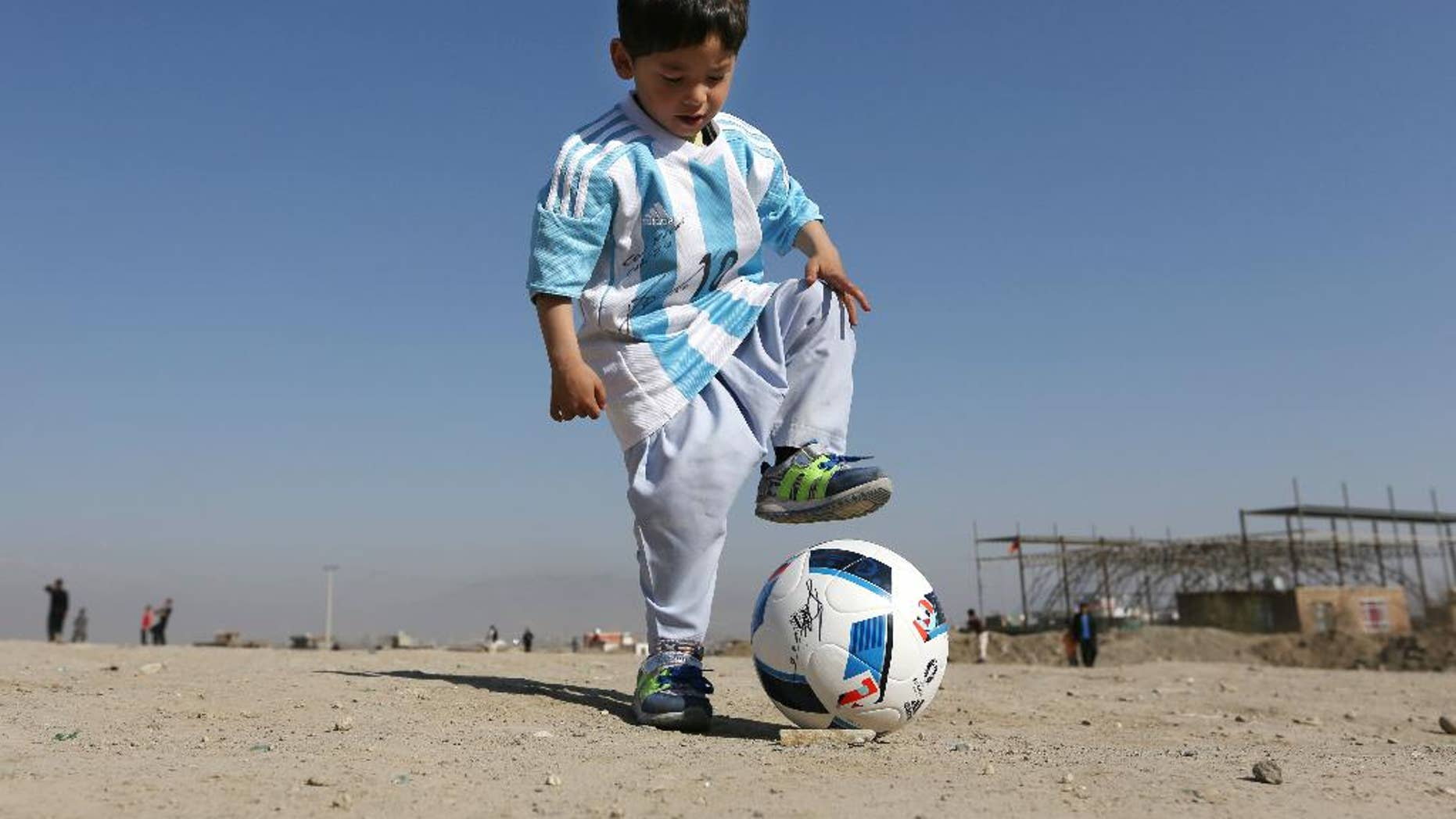 FILE - In this Friday, Feb. 26, 2016 file photo, Murtaza Ahmadi, a five-year-old Afghan Lionel Messi fan plays with a soccer ball during a photo opportunity as he wears a shirt signed by Messi, in Kabul, Afghanistan. The father of Ahmadi says the family was forced to leave Afghanistan amid constant telephone threats. (AP Photo/Rahmat Gul, File)