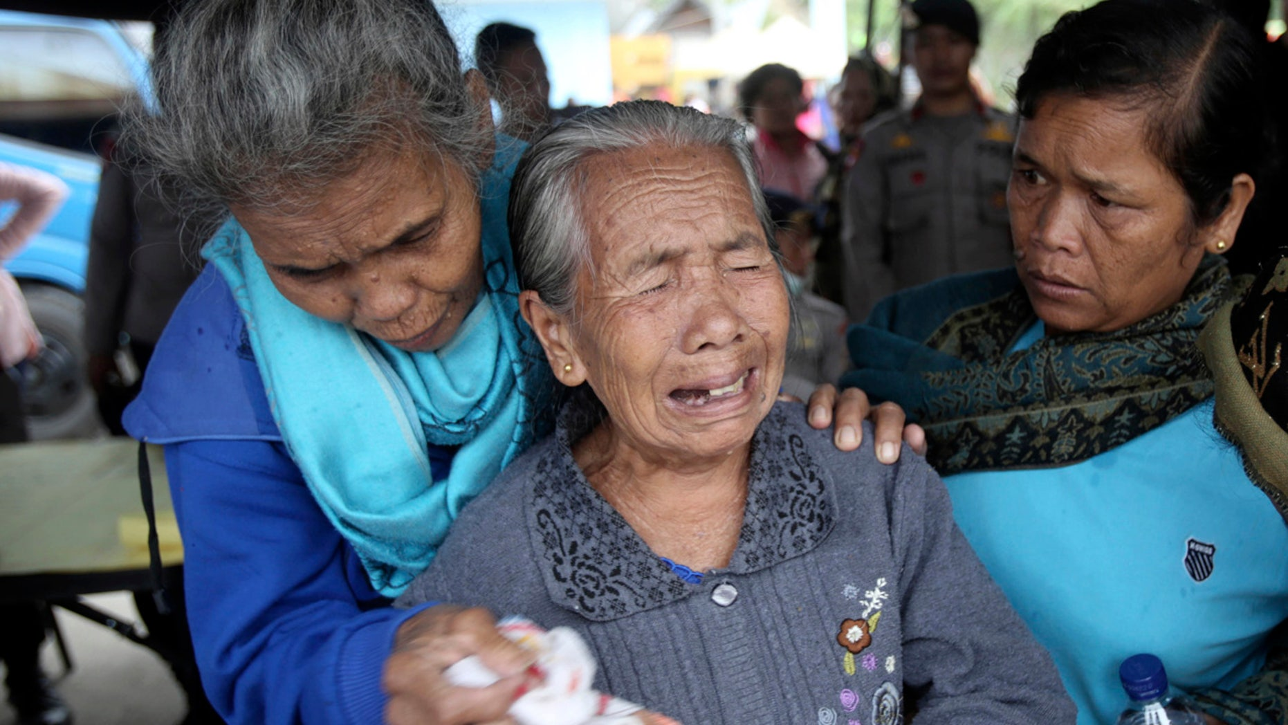 Relatives of victims of a sunken ferry weep as they wait for news at Tigaras port in Lake Toba, North Sumatra, Indonesia.