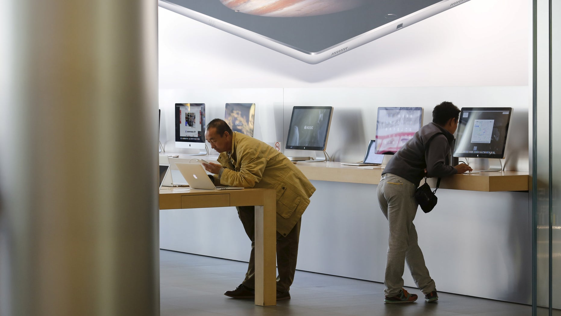 Men try apple's MacBook laptops at an apple store in Beijing. (REUTERS/Kim Kyung-Hoon)