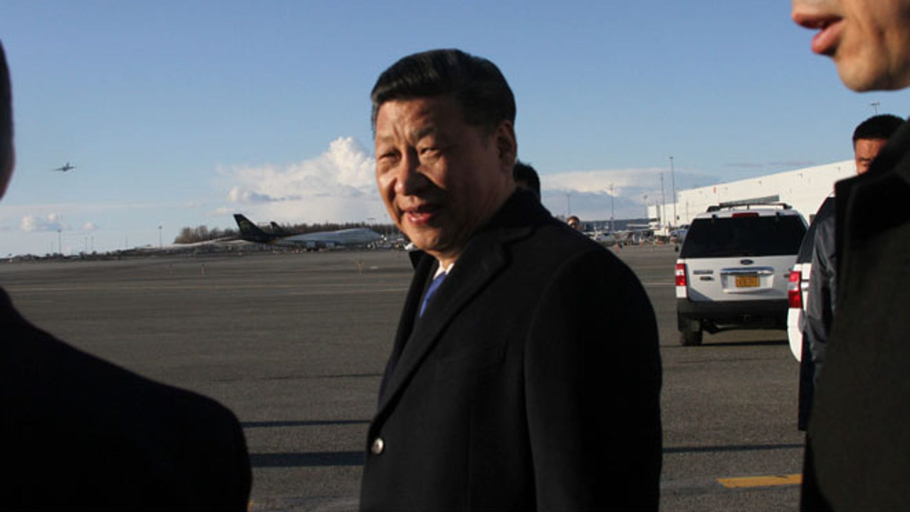 Chinese President Xi Jinping, left,, smiles after getting off his plane for a refueling stop in Anchorage