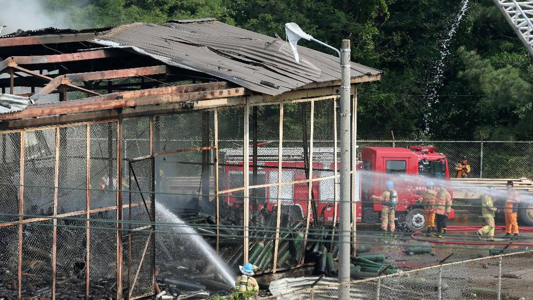 Firefighters extinguish a fire at Camp Carroll in Chilgok, South Korea, Thursday, May 19, 2016. An oxygen tank blew up at the U.S. military base in South Korea, causing a fire, but there were no reports of casualties. The U.S. military said it was investigating the cause of the blast Thursday at Camp Carroll, 280 kilometers (175 miles) southeast of the Seoul. (Kim Jun-beum/Yonhap via AP) KOREA OUT